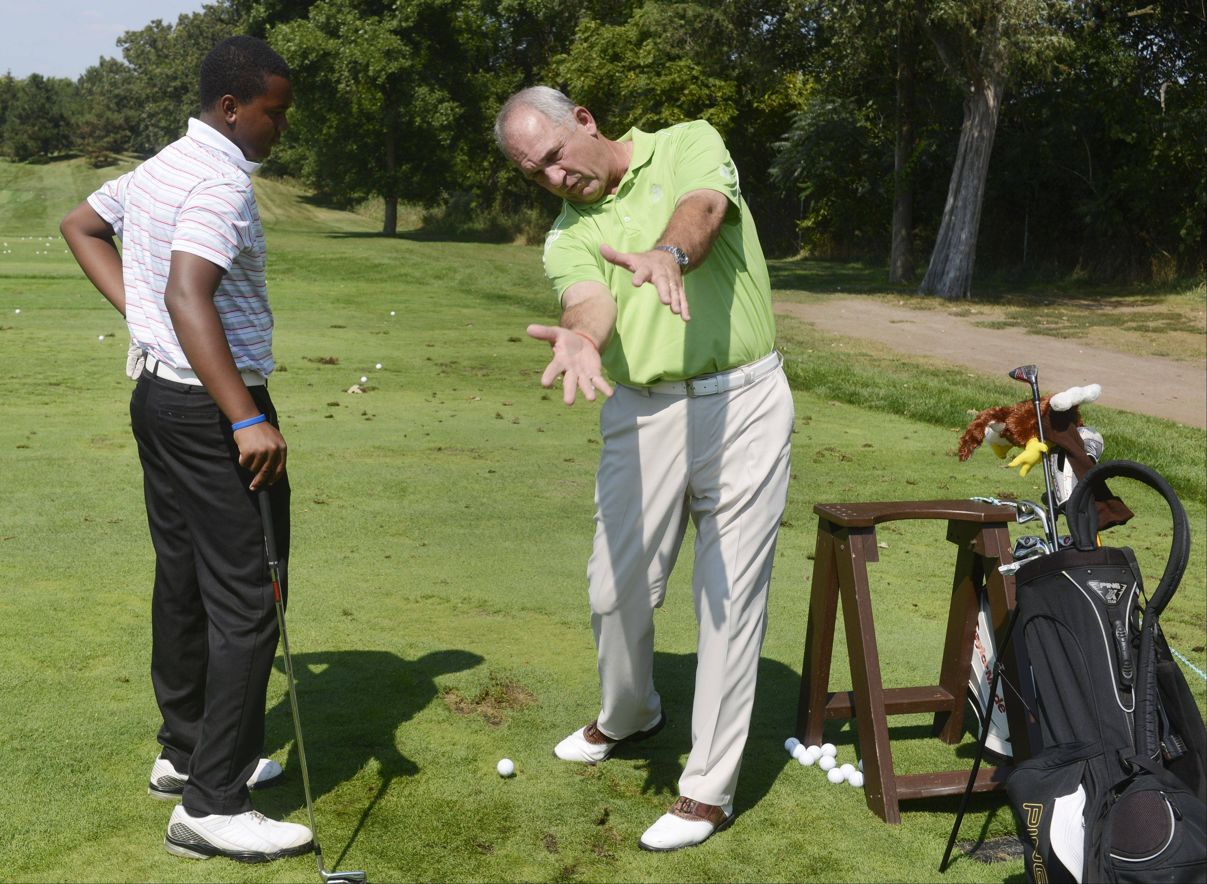 Head golf pro Jim Sobb gives advice to Trevor Britton, 14, of Wadsworth during the First Tee golf event at Ivanhoe Club near Mundelein. First Tee uses the game of golf to provide education programs that build character. Thirteen kids were rewarded for their good choices with a special day at Ivanhoe.