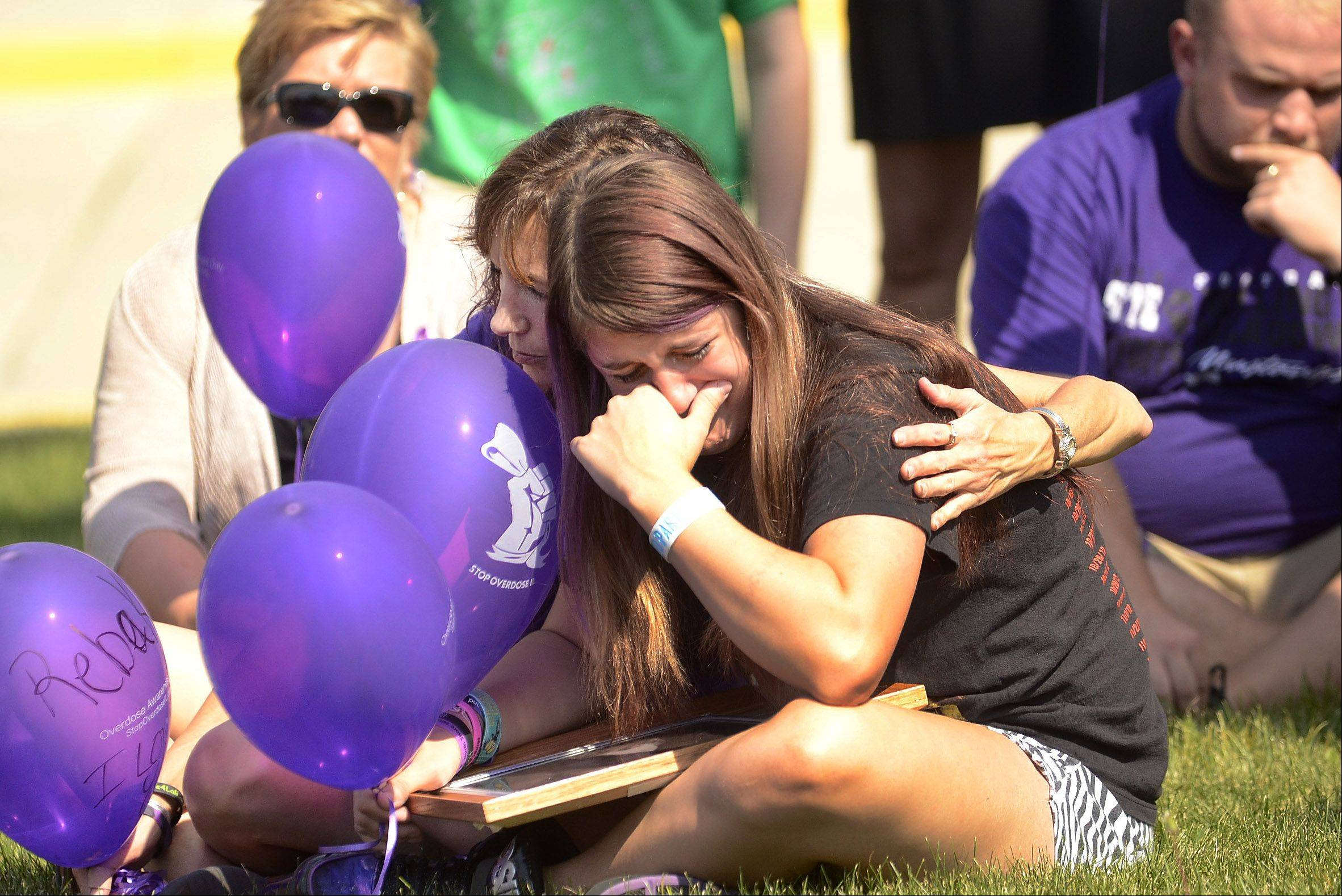 Bre Bjornberg of Schaumburg is consoled by her mom Kari Bjornberg as they remember Bre's brother Michael who died of an overdose during the Overdose Awareness Week ceremony at Roosevelt University's Schaumburg campus.