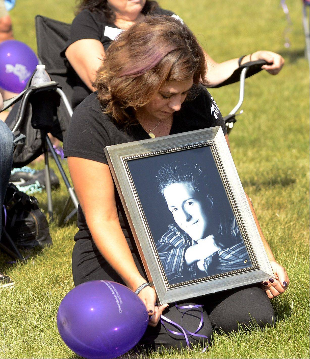 Kristen Gutierrez of Aurora holds a picture of her brother Louie Miceli of Medinah, who died of a heroin overdose last year at the age of 24, during a ceremony honoring those who died during Saturday's overdose awareness event.