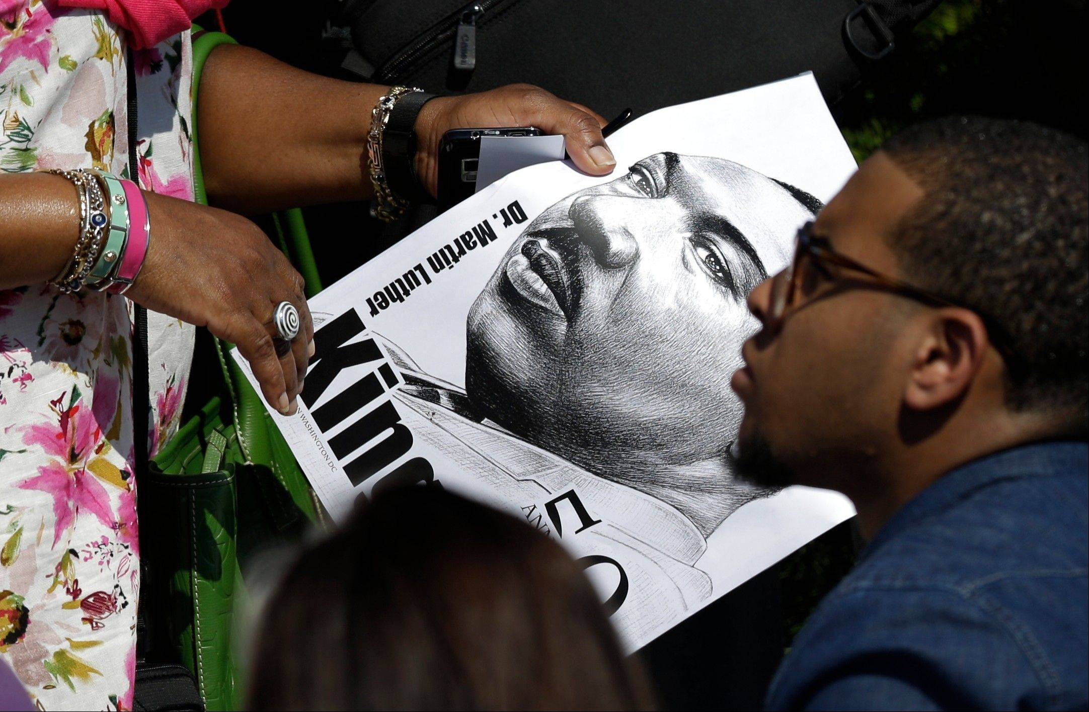A woman carries a sign with the image of Martin Luther King Jr. on it through the crowd during an event Saturday to commemorate the 50th anniversary of the 1963 March on Washington at the Lincoln Memorialn Washington.