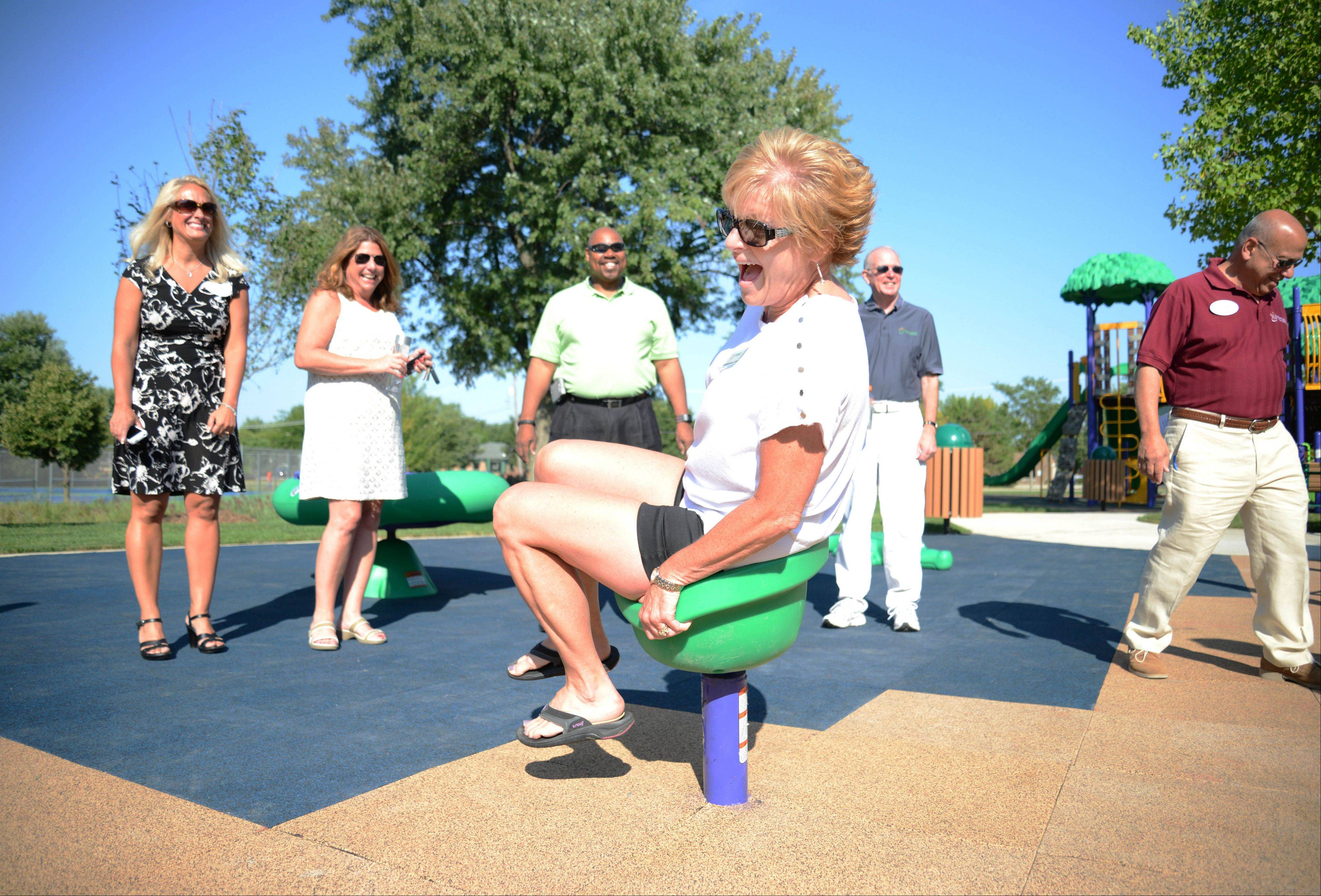 Park board Commissioner Karen Johns tries the spinning seat Saturday during the grand opening of the new Sunnyside Accessible Park in Bloomingdale.