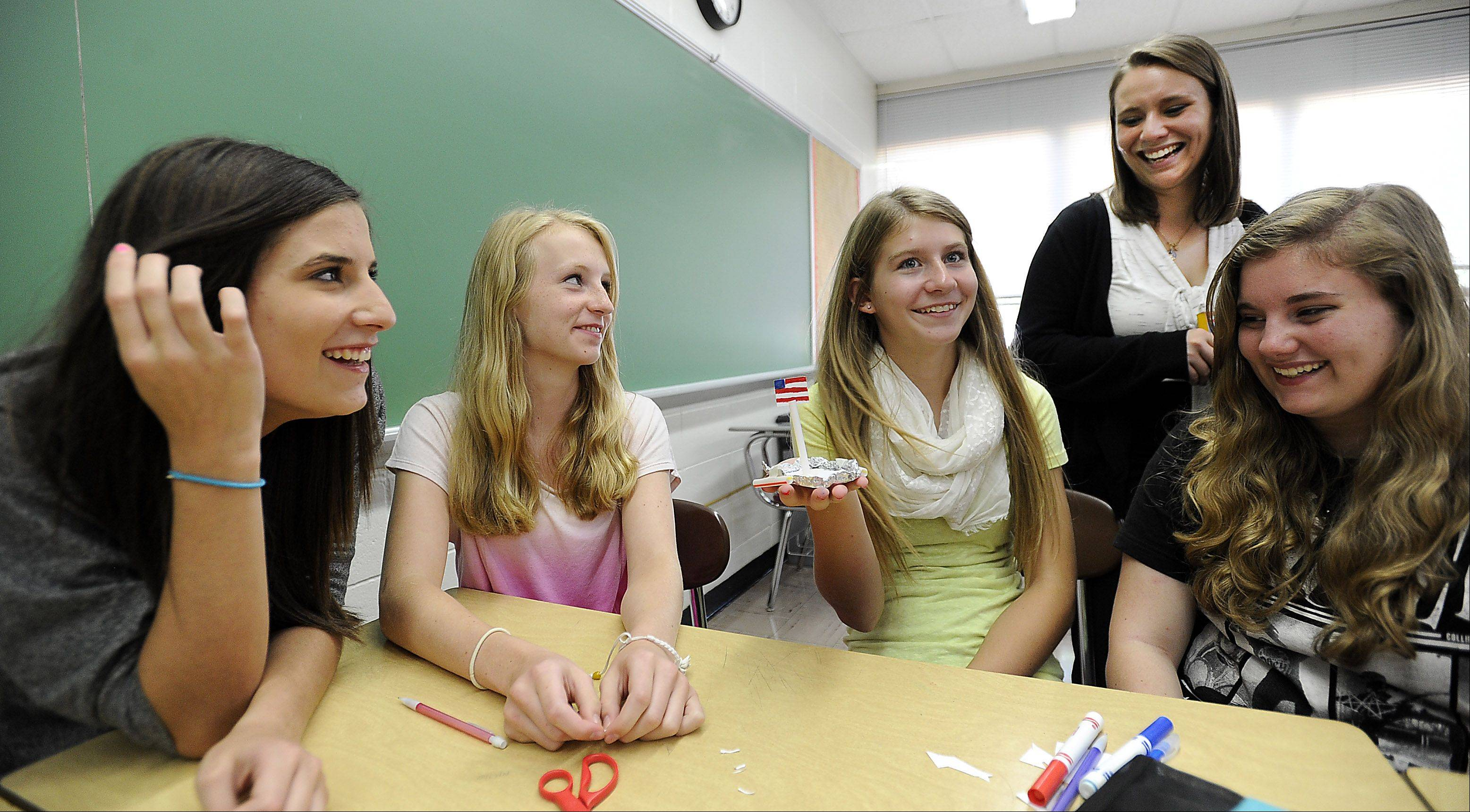 New Mundelein High School math teacher Maggie Sharp looks over the paper boat constructed by Anjelika McFeely, 14, Claire Whitemarsh, 14, Annie McGarth, 14, and Jenna Geary, 14, during their first day of class. They would later see how many pennies it would hold while floating in water -- 99 pennies is the current record.