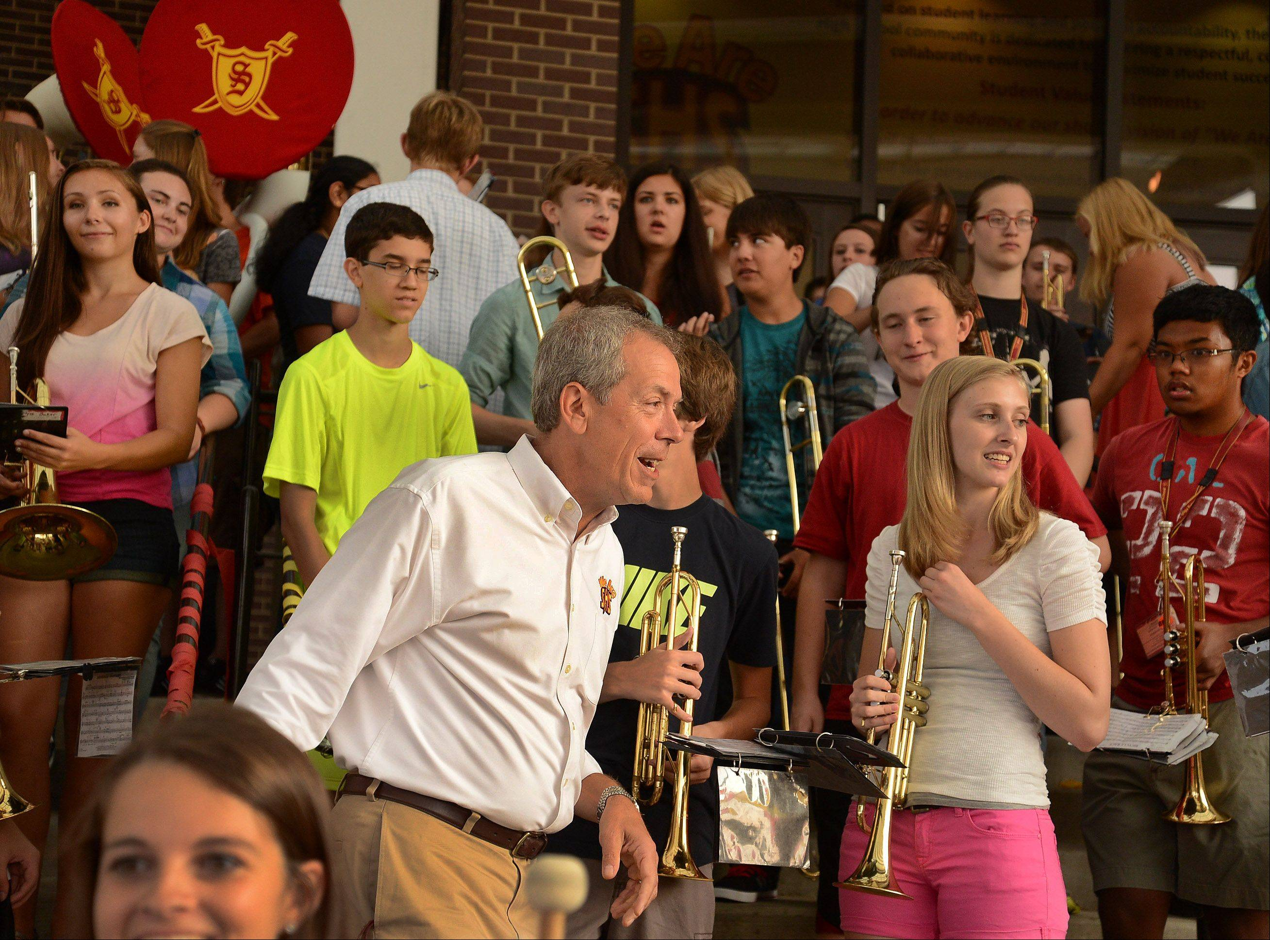 Schaumburg High School band director Kevin Miller leads the marching band in a performance on the front steps of the building during the first day of his last year teaching at the school.