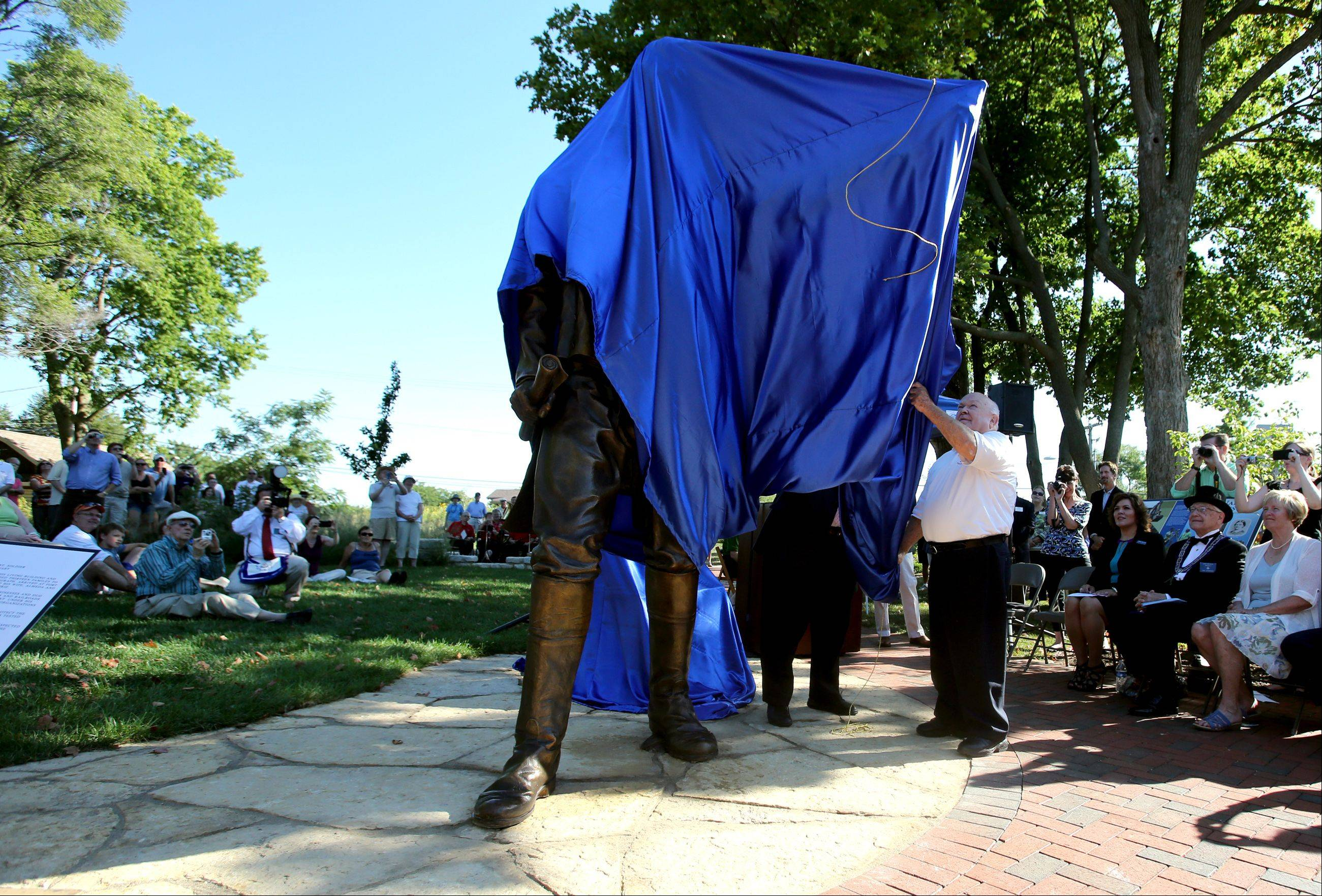 Naperville Mayor George Pradel unveils a sculpture of town founder Joseph Naper Friday at the Naper Homestead historic interpretive site. The 1,500-pound bronze sculpture is 9 1/2 feet tall.