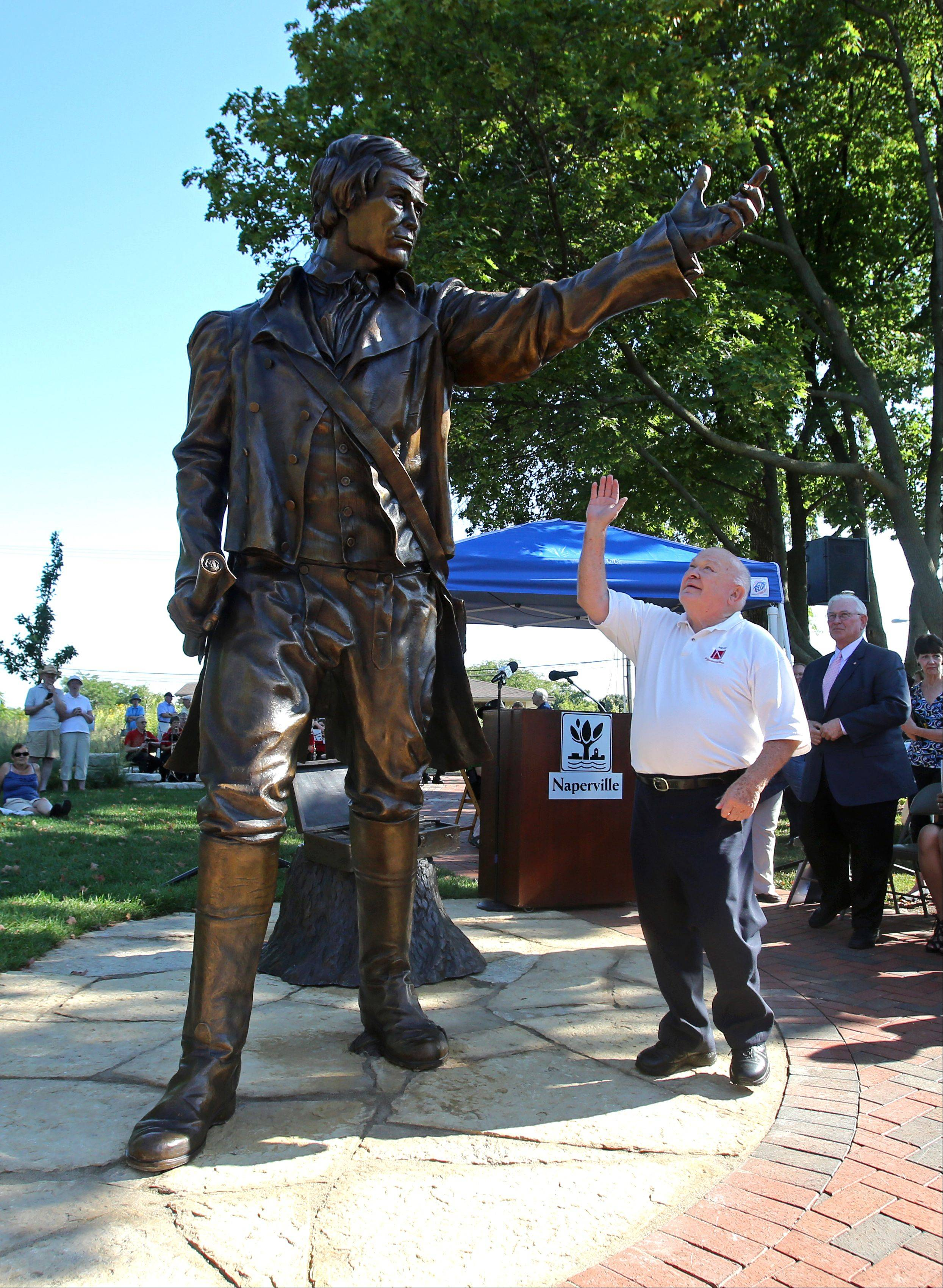 Naperville Mayor George Pradel looks up to the newly unveiled Joseph Naper statue at the Naper Homestead and tries to give the town's founder a high-five. The $185,000, 1,500-pound sculpture is cast in bronze and accompanied by a box of land surveyor's tools.