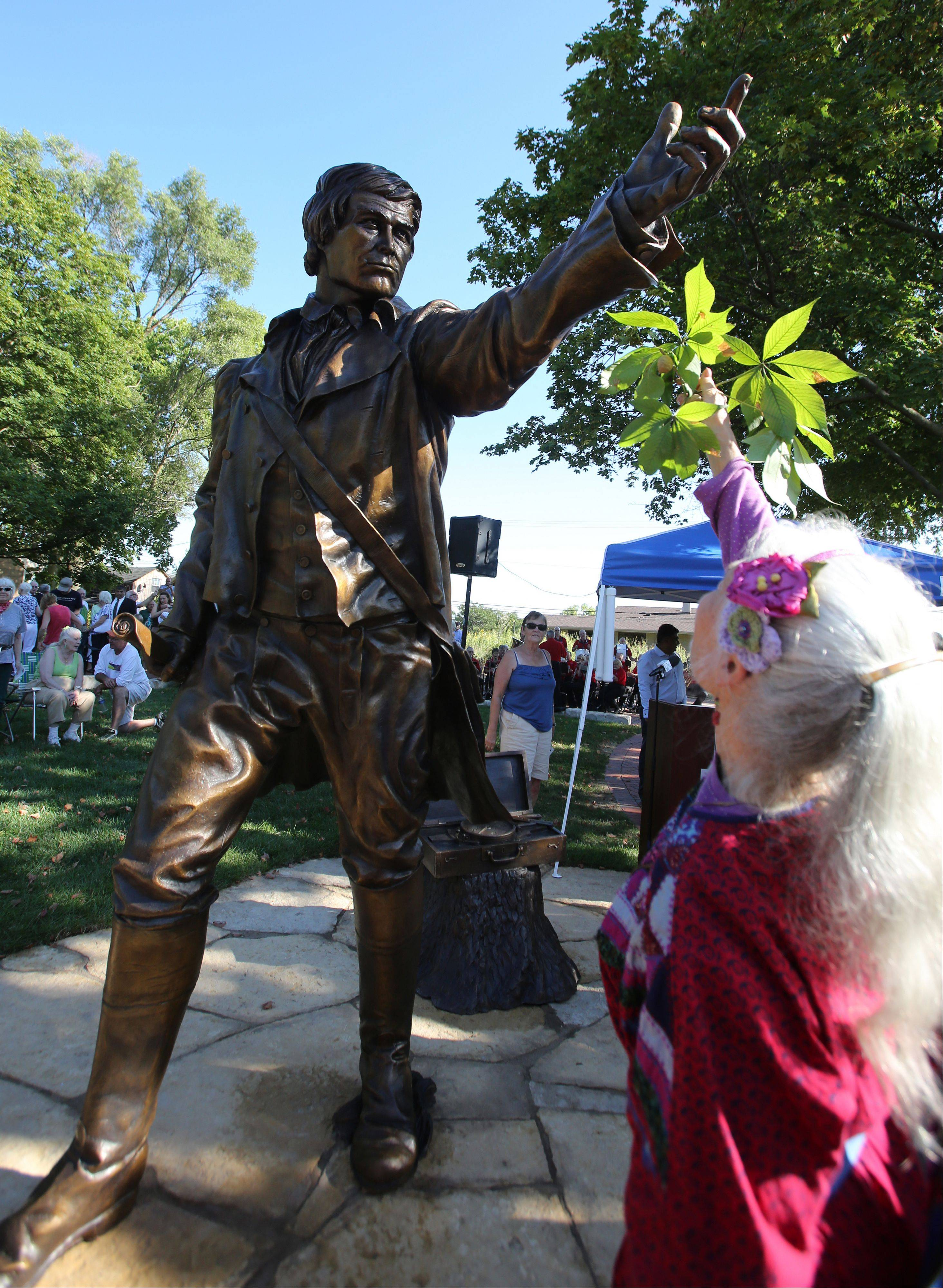 Carolyn Finzer, a fifth generation Naperville resident, offers a sprig of Buckeye tree leaves to the sculpture of town founder Joseph Naper on Friday following a dedication at the Naper Homestead historic interpretive site.