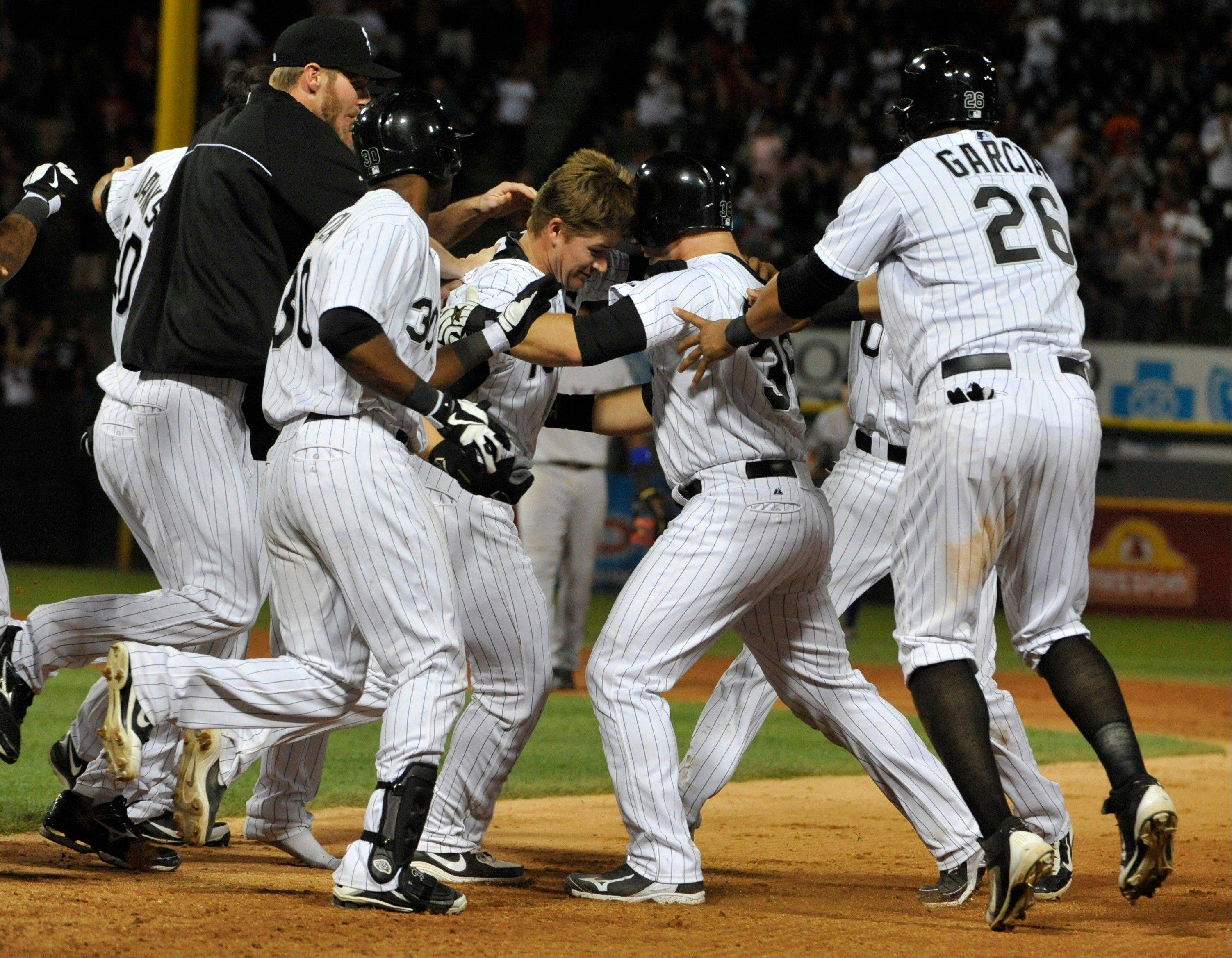 Josh Phegley, middle, is swarmed by his White Sox teammates after getting the game-winning hit Saturday night against the Rangers.
