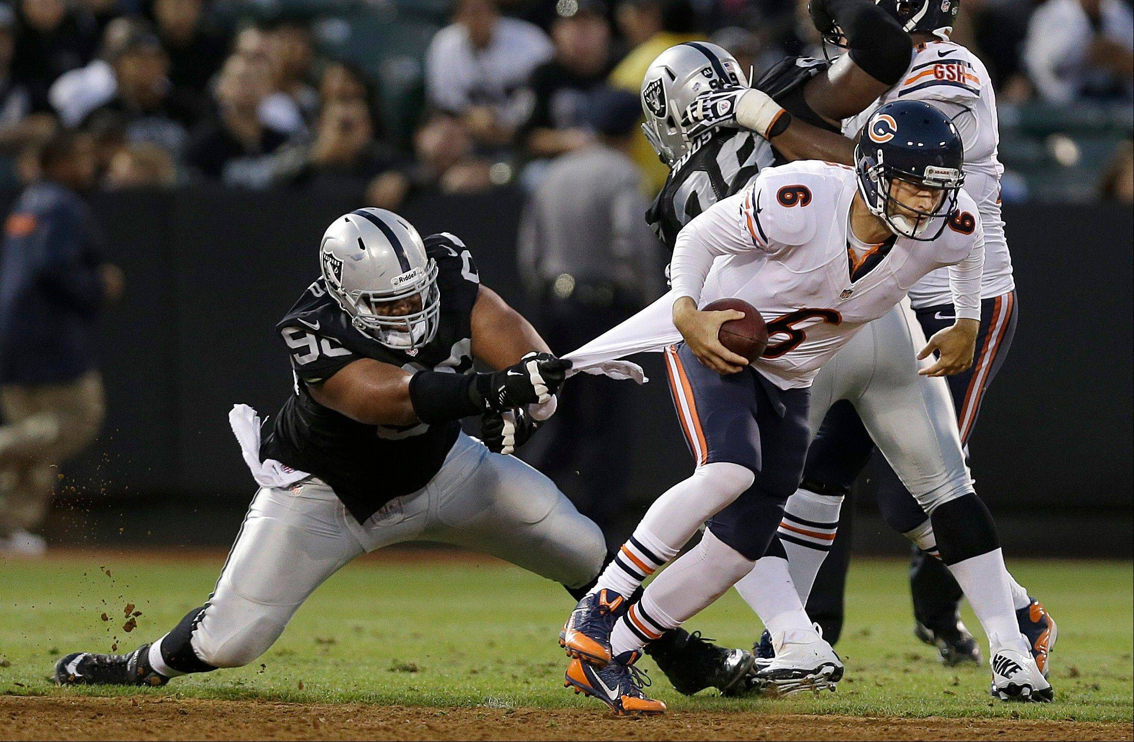 Chicago Bears quarterback Jay Cutler (6) escapes the grasp of Oakland Raiders defensive tackle Vance Walker (98) during the second quarter.