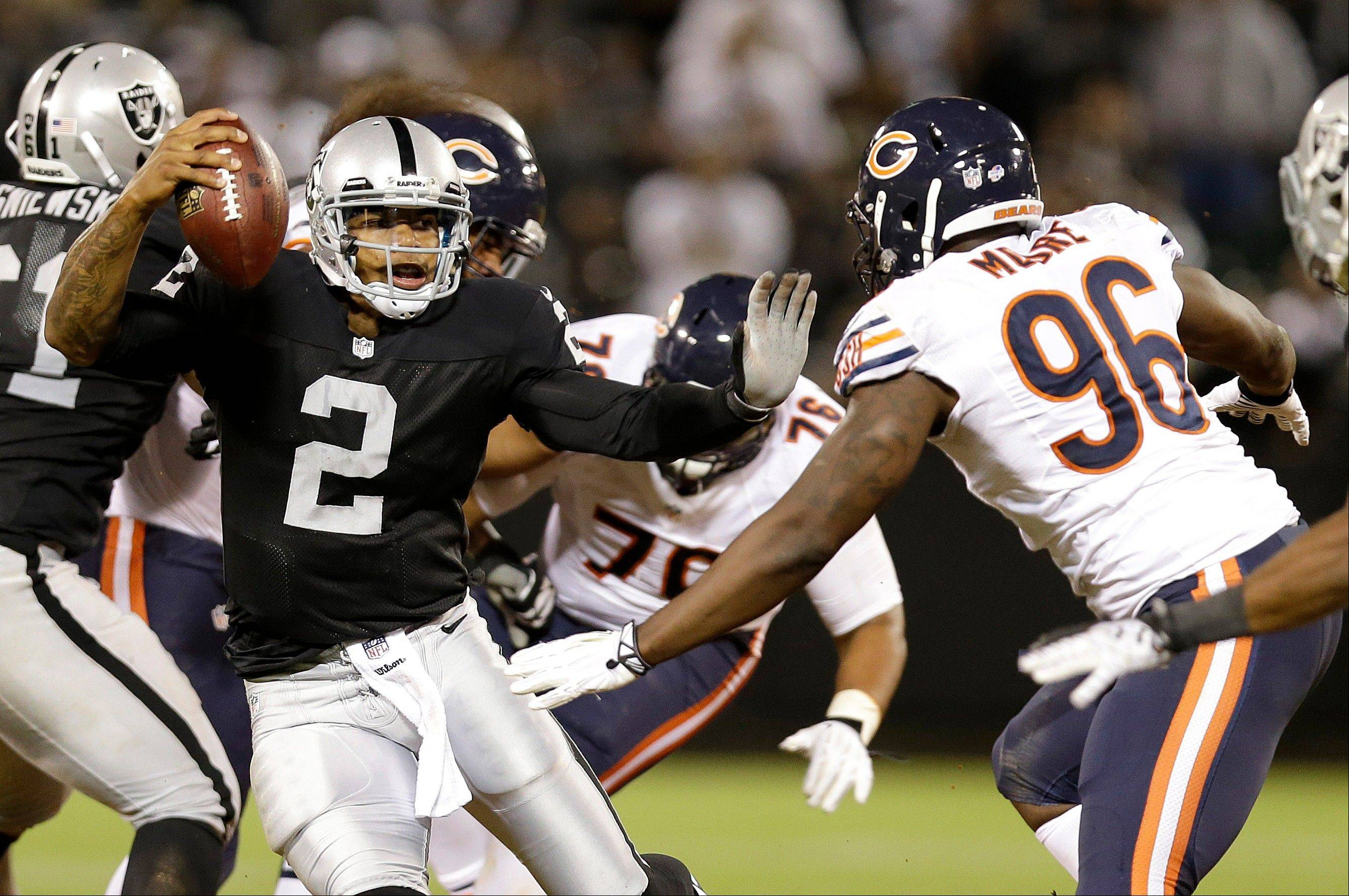 Oakland Raiders quarterback Terrelle Pryor (2) avoids Chicago Bears defensive end Kyle Moore (96) on his 25-yard touchdown run during the third quarter.
