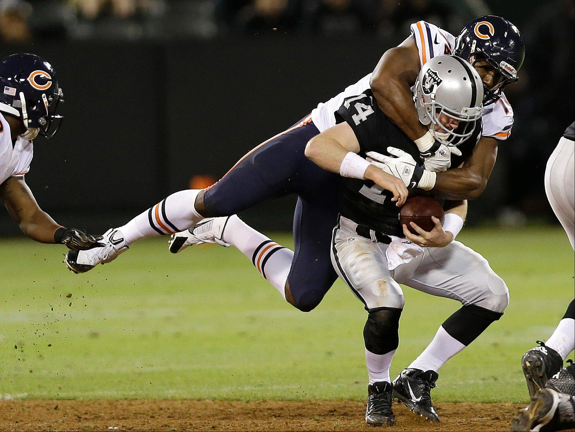 Chicago Bears defensive end Cornelius Washington sacks Oakland Raiders quarterback Matthew McGloin (14) during the fourth quarter.