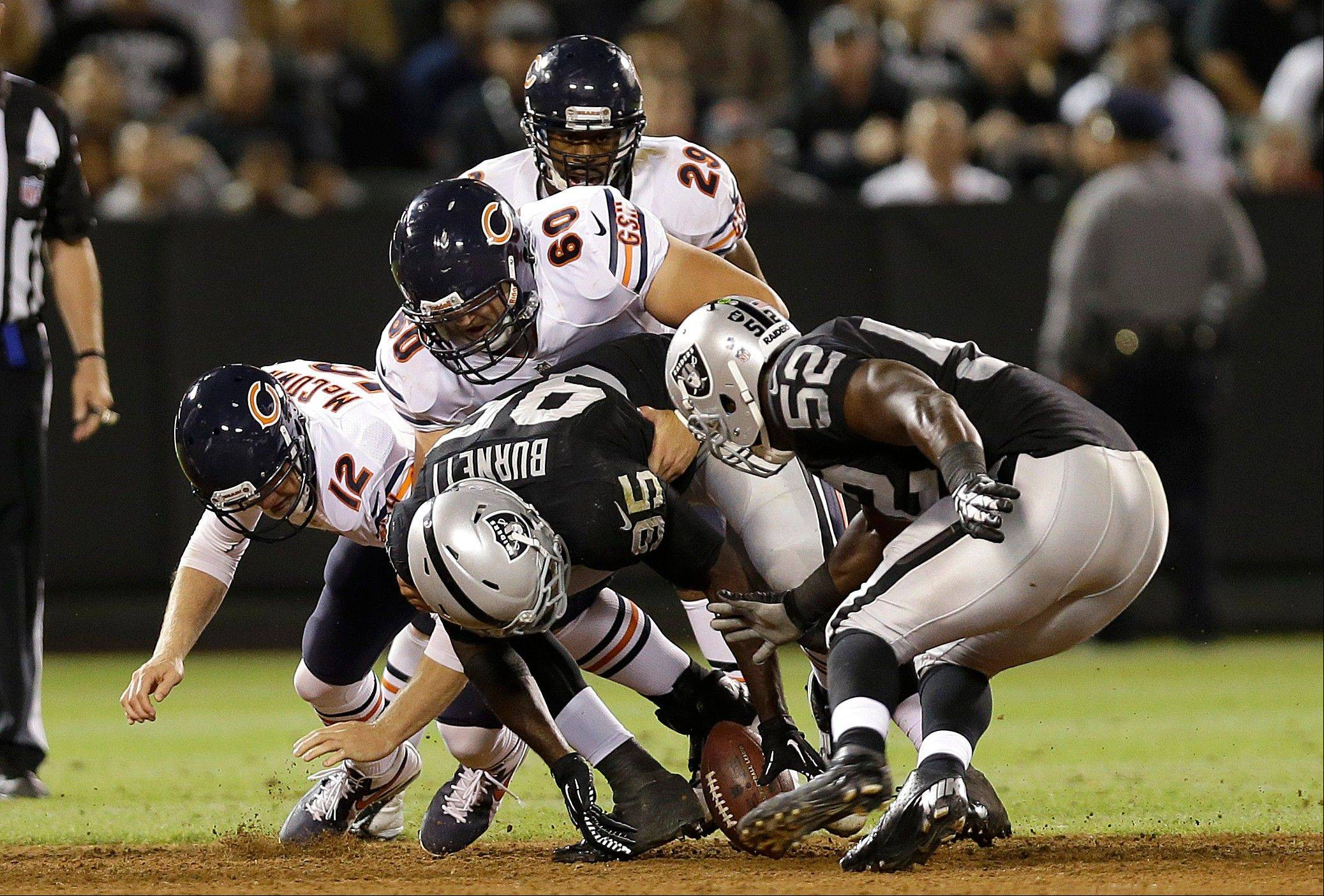 Oakland Raiders linebacker Kaelin Burnett (95) and linebacker Omar Gaither (52) try to recover a fumble by Chicago Bears quarterback Josh McCown (12) during the third quarter .