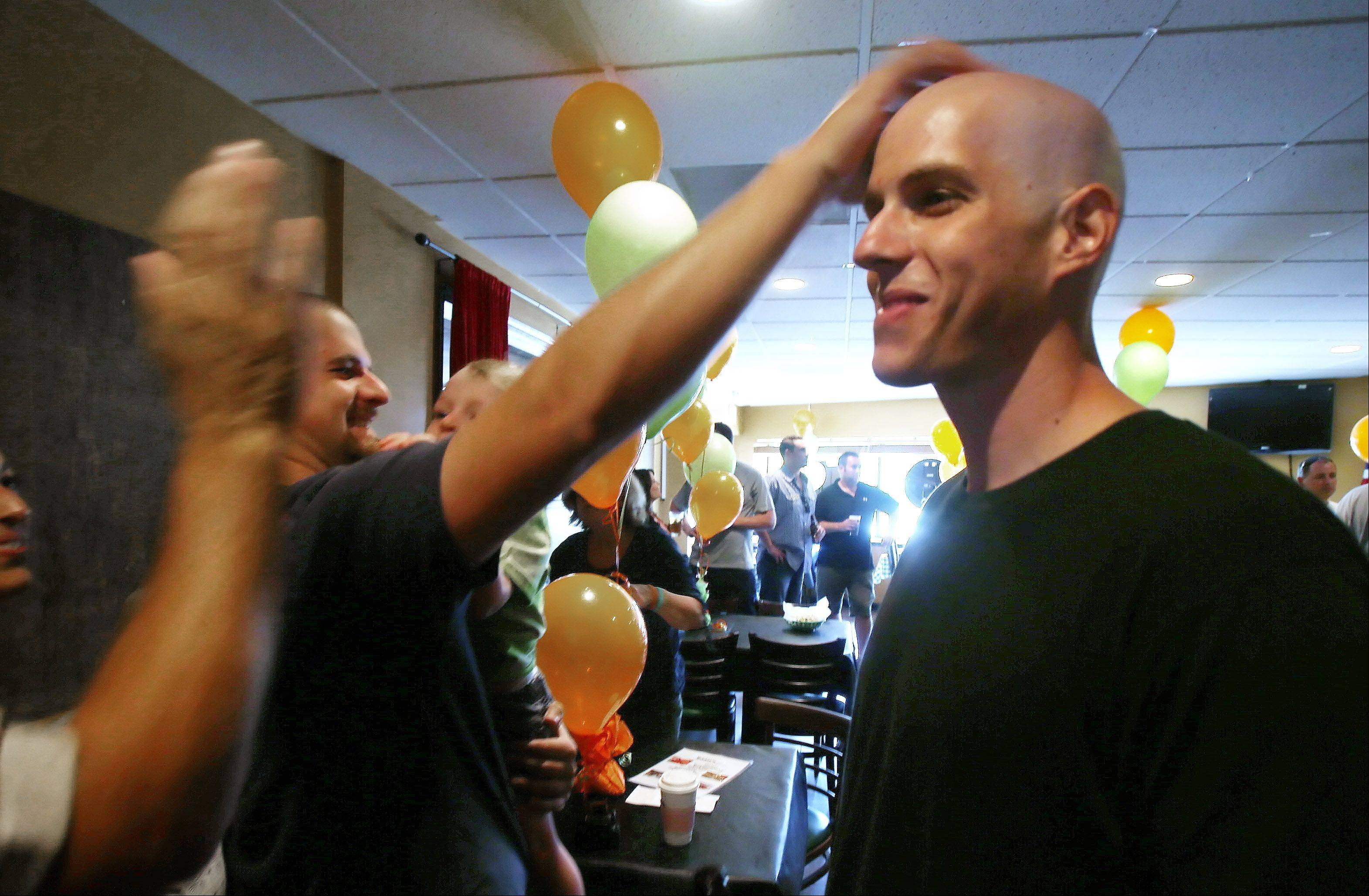 "Sean McCarthy rubs the head of his brother, Ryan, during the Ryan ""McCancer"" Party Sunday at Eddie's in Arlington Heights. The charity fundraiser was in honor of 25-year-old Buffalo Grove firefighter Ryan McCarthy, of Rolling Meadows, who is battling lymphoma. Money raised benefitted the Leukemia & Lymphoma Society."