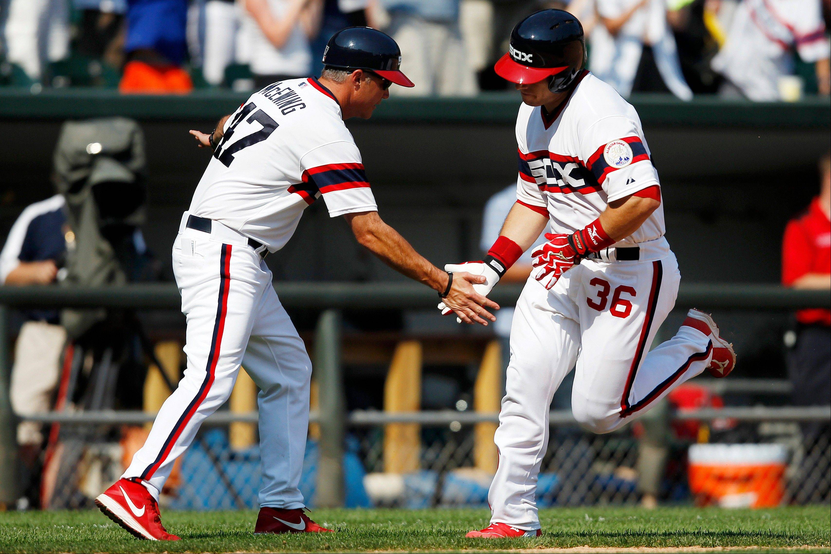 White Sox hitter Josh Phegley is congratulated by third base coach Joe McEwing after hitting a home run against the Texas Rangers during Sunday�s seventh inning at U.S. Cellular Field.