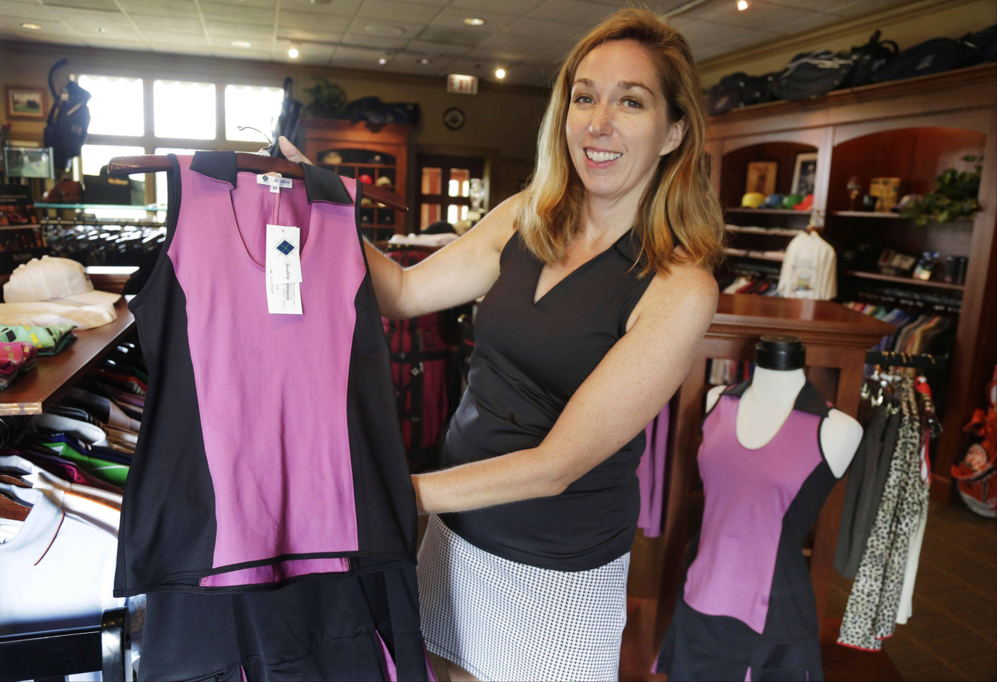 Kelly Daugherty, co-owner of Smashing Golf & Tennis, with her clothing line in the pro shop at Biltmore Country Club in North Barrington. The owners of Smashing Golf & Tennis can't take vacations this summer because they're training new sales people for the company's line of active wear for women. They also are getting their spring styles ready and have to be around for last-minute orders, as this is high season for golfers and tennis players.
