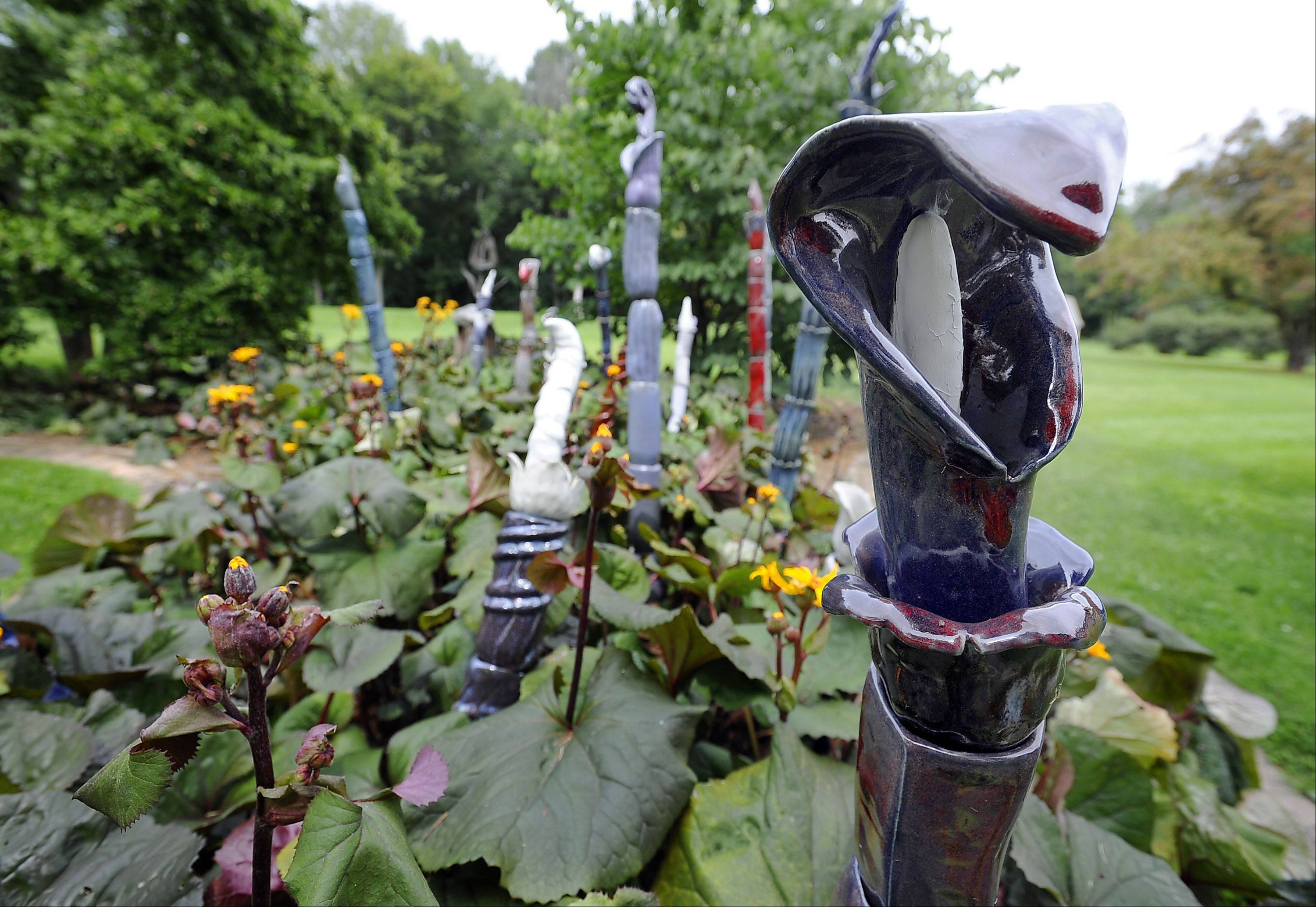 Segmented ceramic whips with glazes in various colors create an Alice in Wonderland scene in one of Lynn Rushing's gardens.