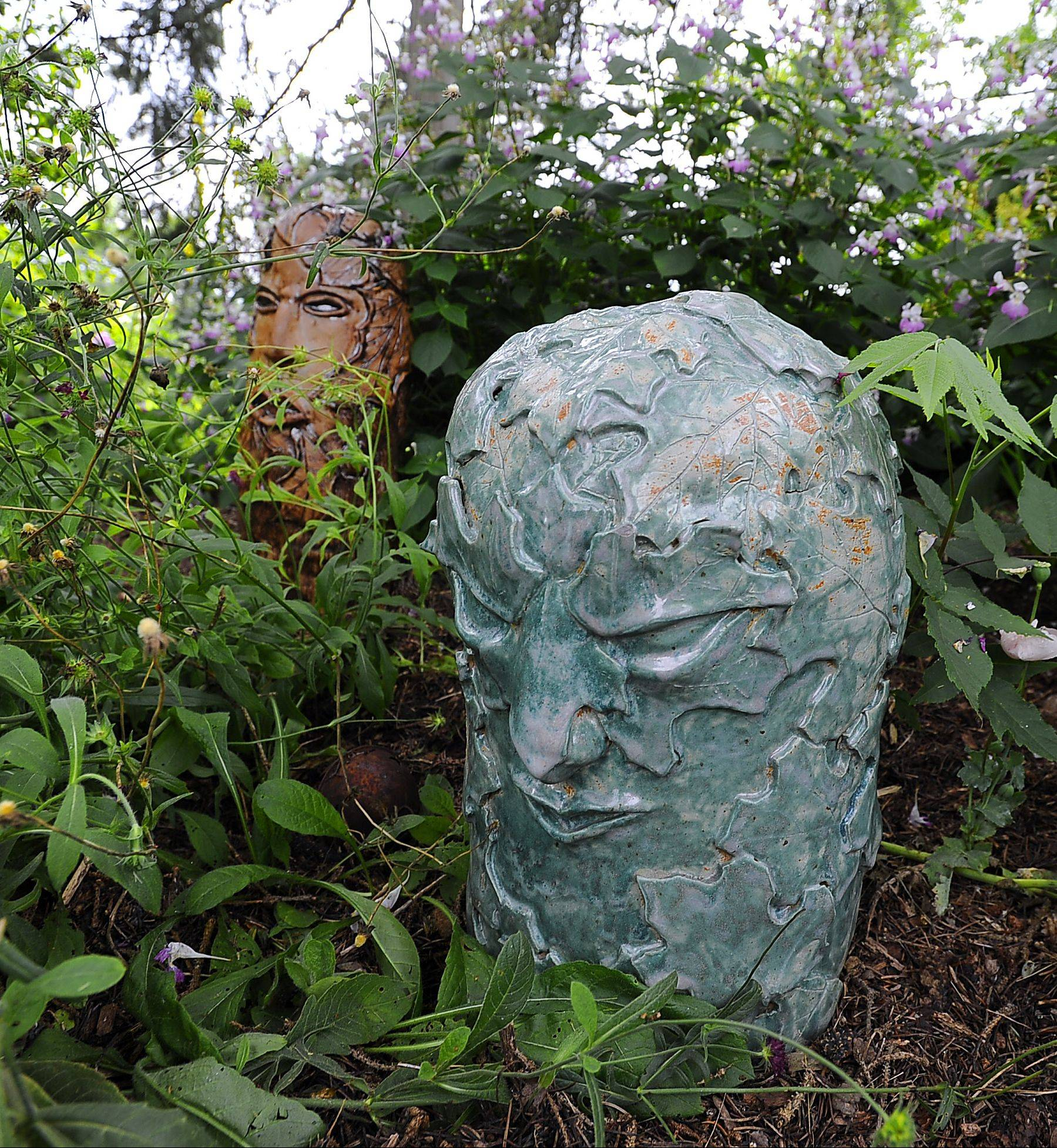 Lynn Rushing of Barrington Hills says the Green Man in her garden is an ancient symbol of Nature still celebrated today. In the background lurks the Wood Man.
