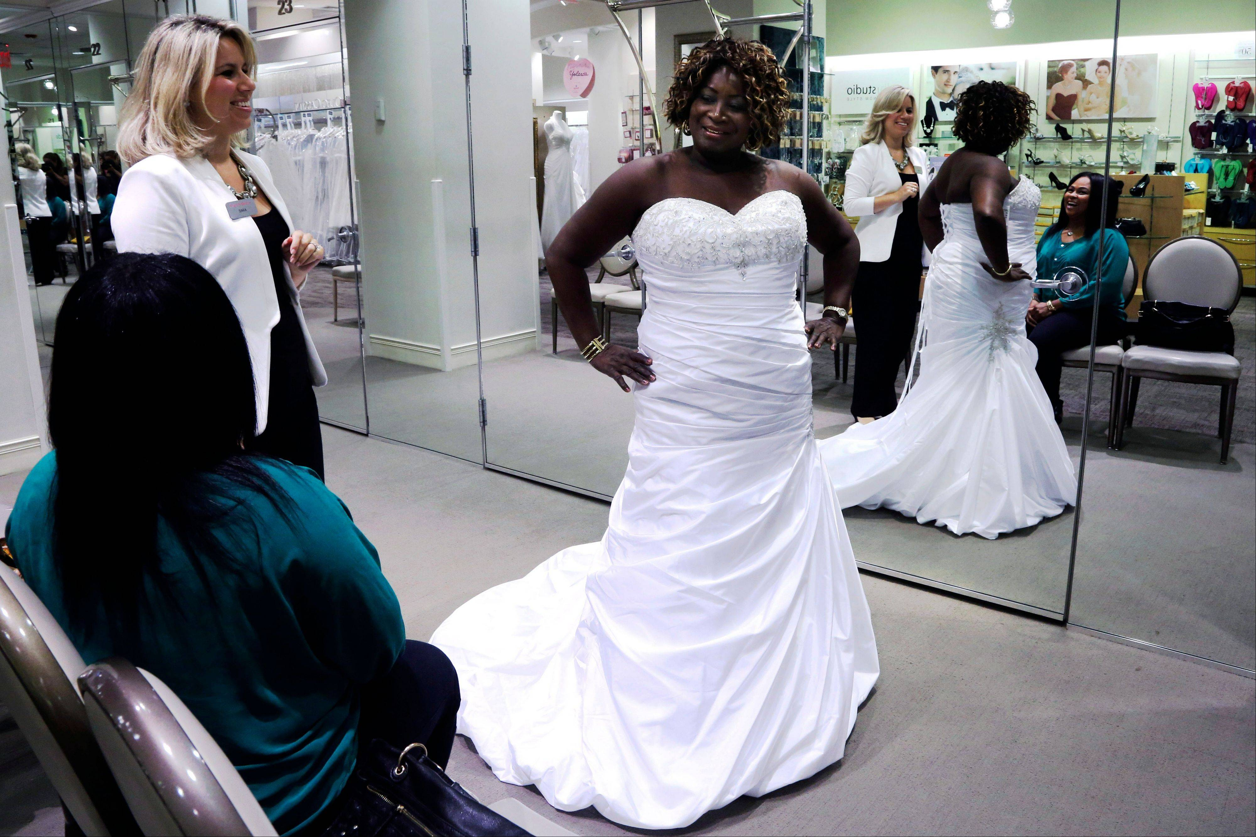 Sara Musillo, assistant store manager at David's Bridal in New York assists Yolanda Royal, 64, as she tries on wedding dresses with her niece Angelic Lavine.