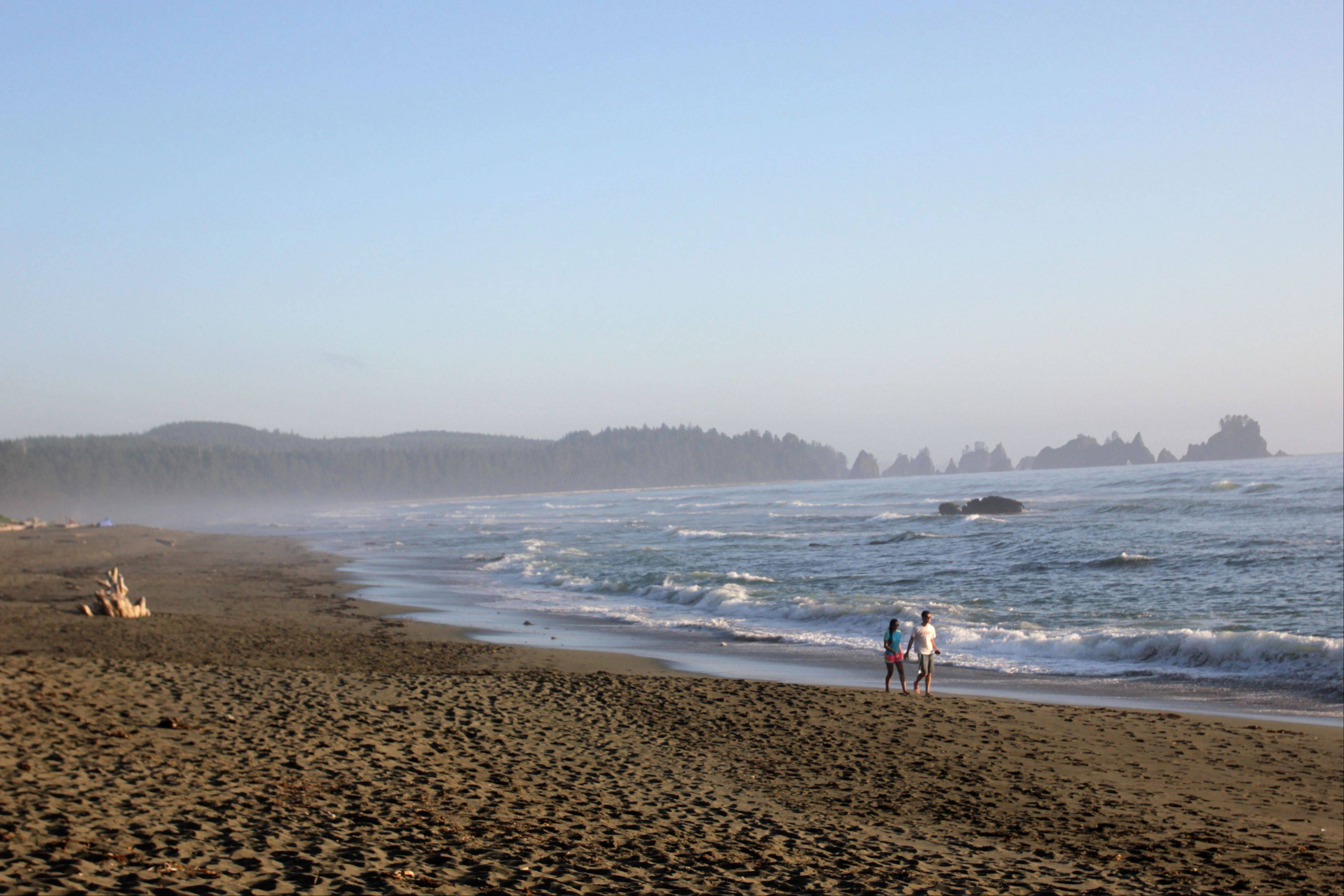 A couple walks down Shi Shi Beach in Washington state's Olympic National Park. One of the most pristine beaches in the state, Shi Shi provides blissful disconnect to hikers and campers at the beach.