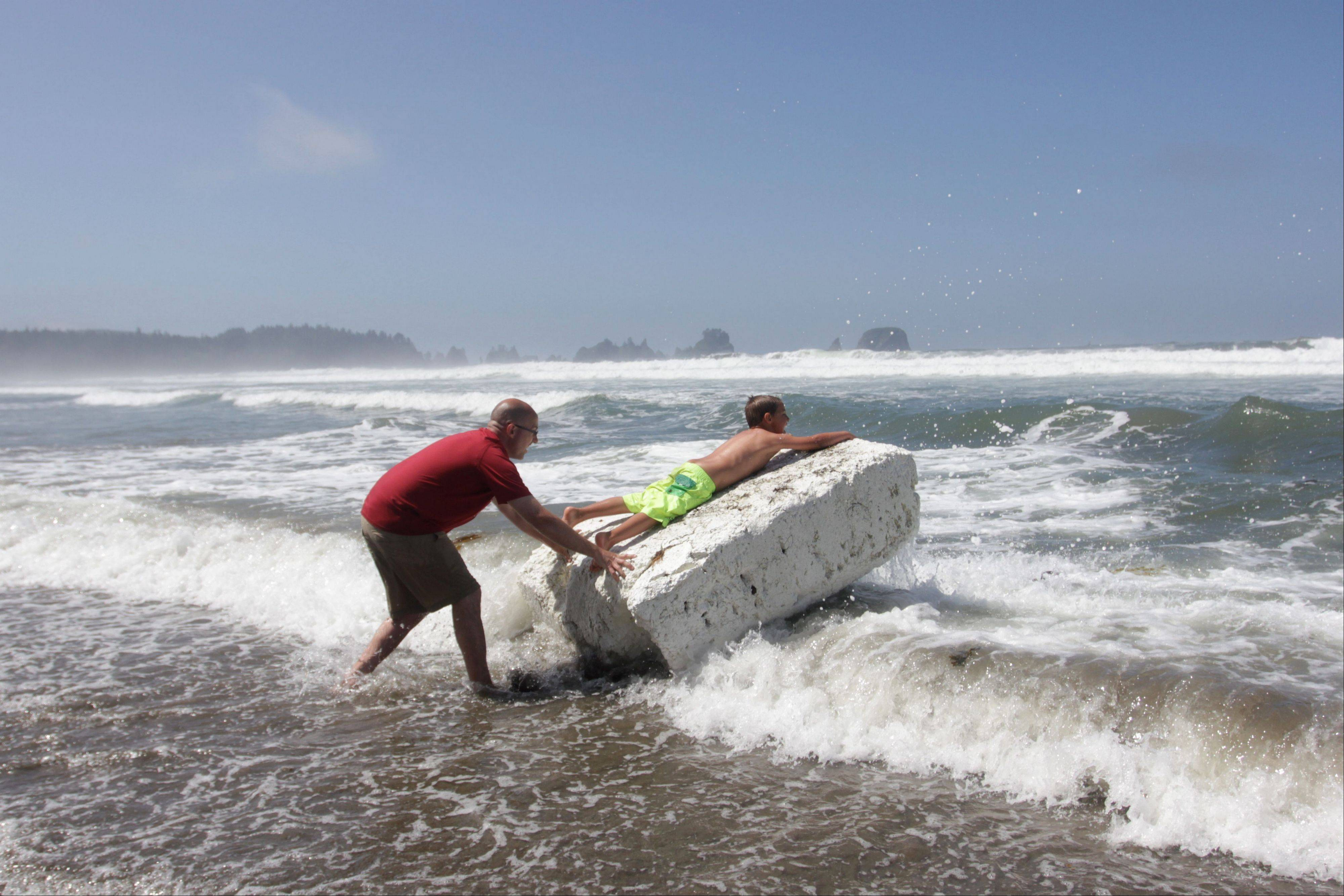 A young boy riding a block of Styrofoam is pushed into the waves by a man at Shi Shi Beach at Olympic National Park.