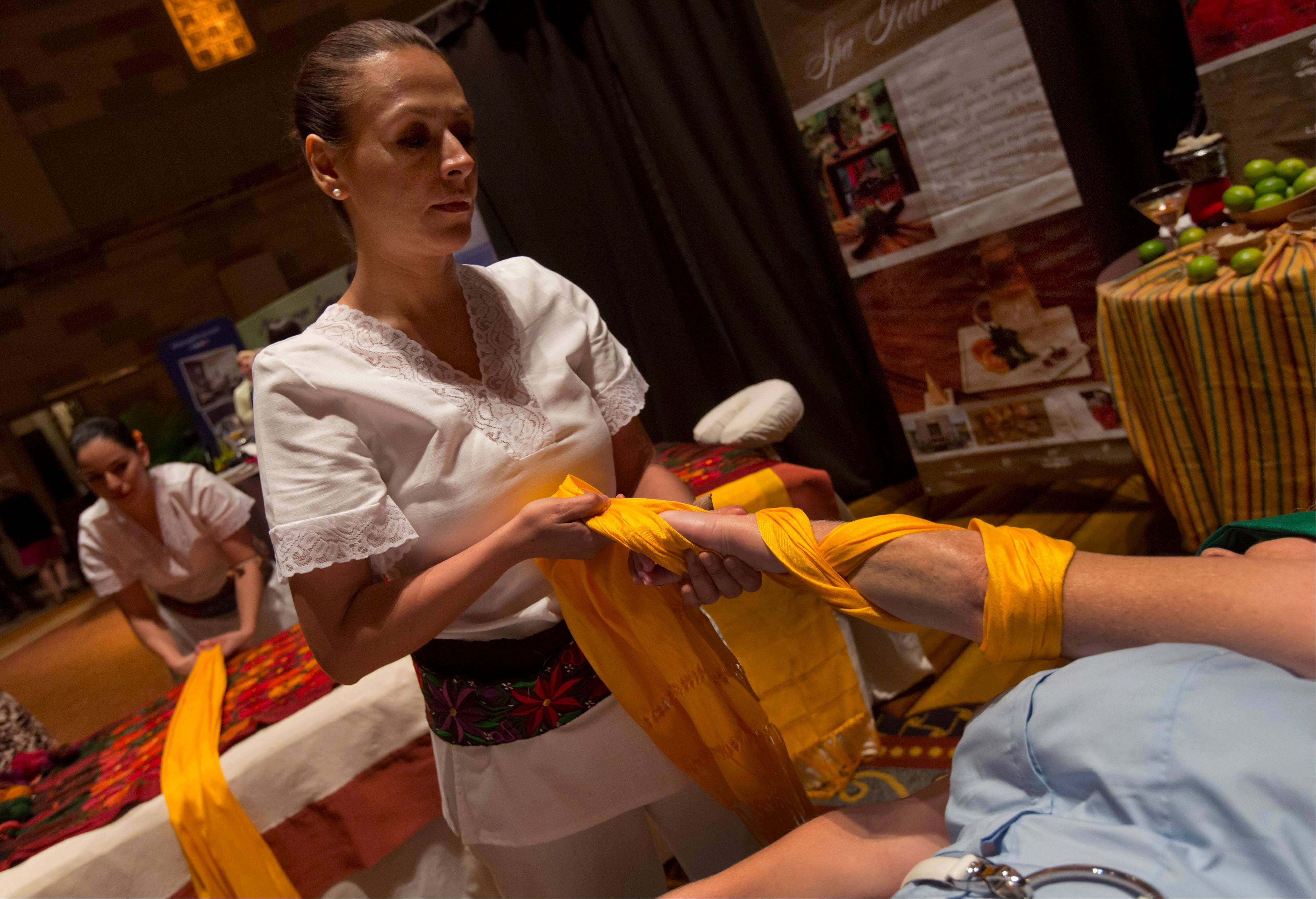 A woman receives a Mayan Royal Massage from Angelica Hurtado at Grand Velas Riviera Maya Spa Resort in Playa del Carmen, Mexico. Brightly colored shawls traditionally used for carrying babies are wrapped around limbs and torso for a gentle stretch treatment preceded by a lemon massage.