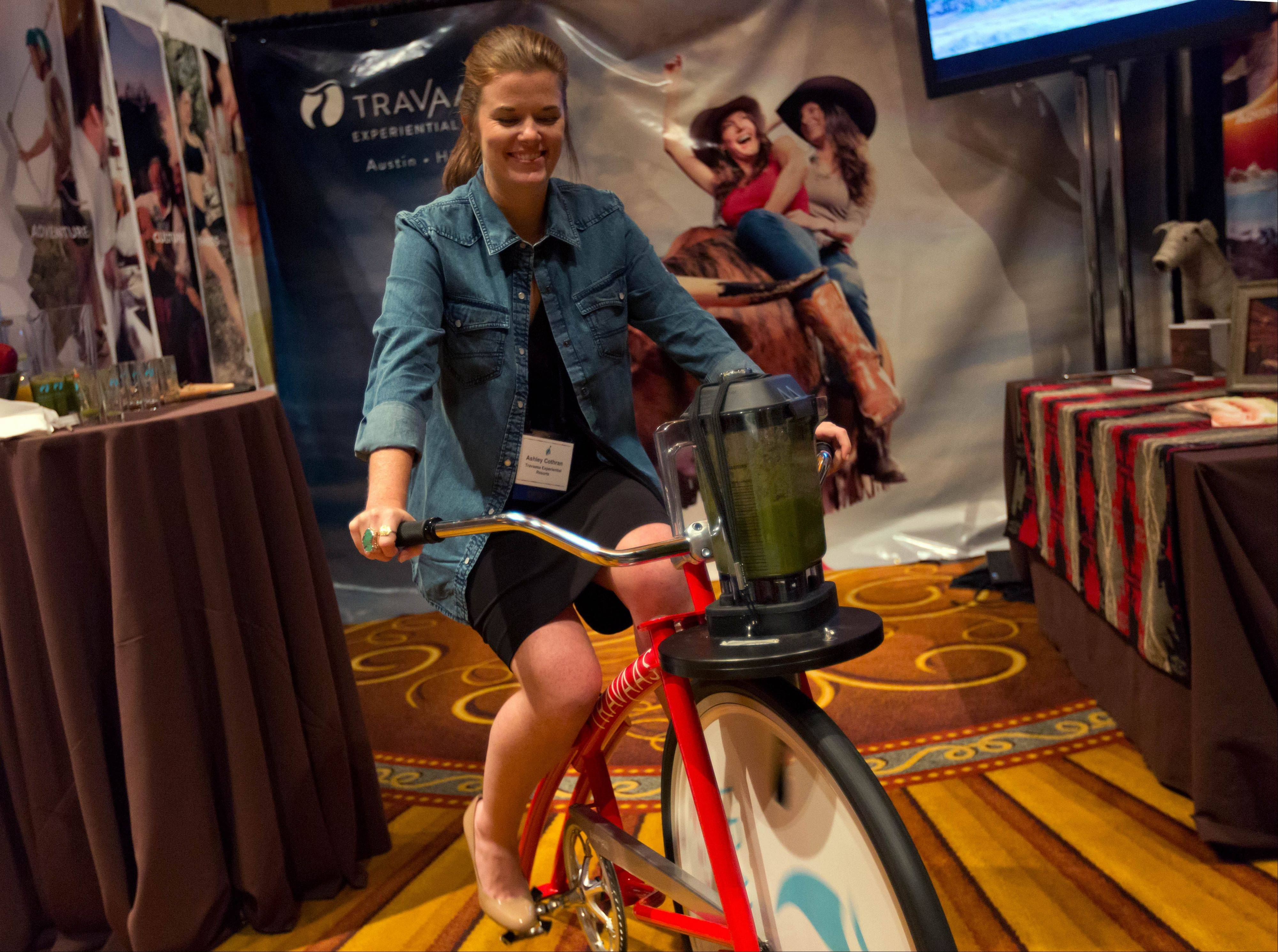 Ashley Cothran, with Travaasa Experiential Resorts, pedals a Fender Blender cycle during the International Spa Association event in New York. It's a stationary bicycle that powers a juicer attached at the handlebars.