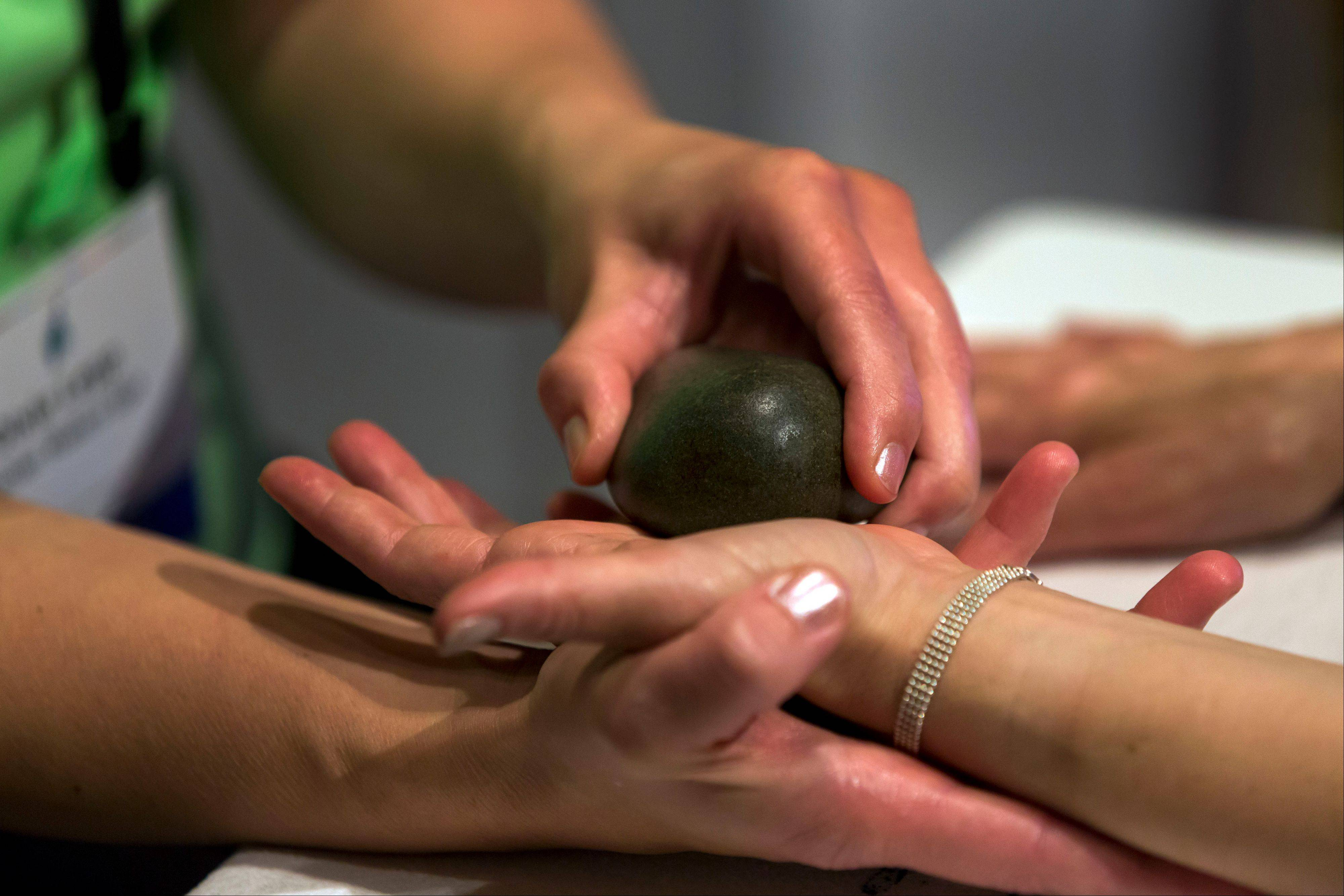 A woman receives a Hand Rescue Citrus Reviver treatment provided by the Kohler Waters Spa.