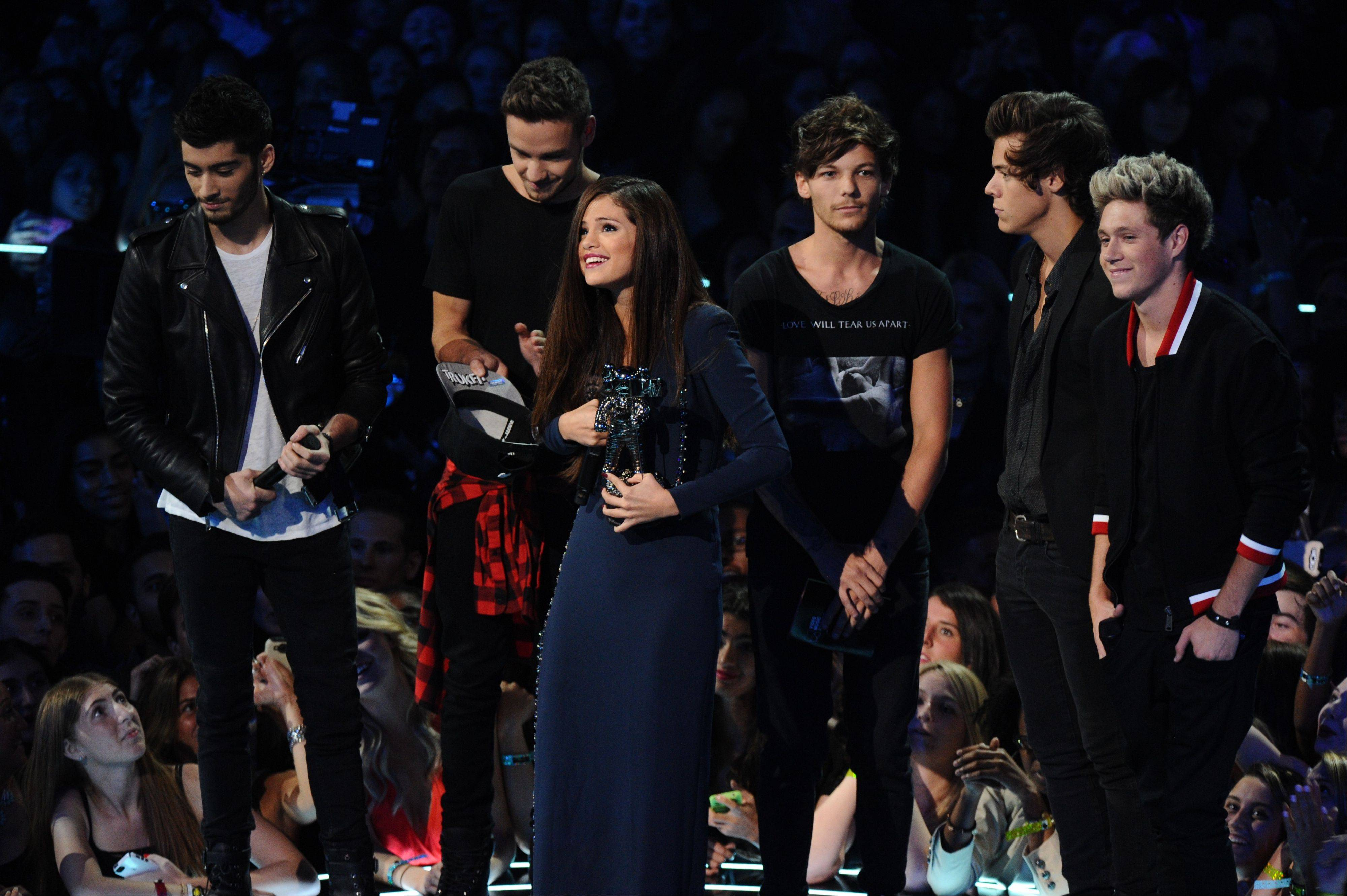 "Zayn Malik, background from left, Liam Payne, Louis Tomlinson, Niall Horan and Harry Styles of One Direction present the award for best pop video for ""Come and Get It"" to Selena Gomez, center, at the MTV Video Music Awards on Sunday, Aug. 25, 2013, at the Barclays Center in the Brooklyn borough of New York."