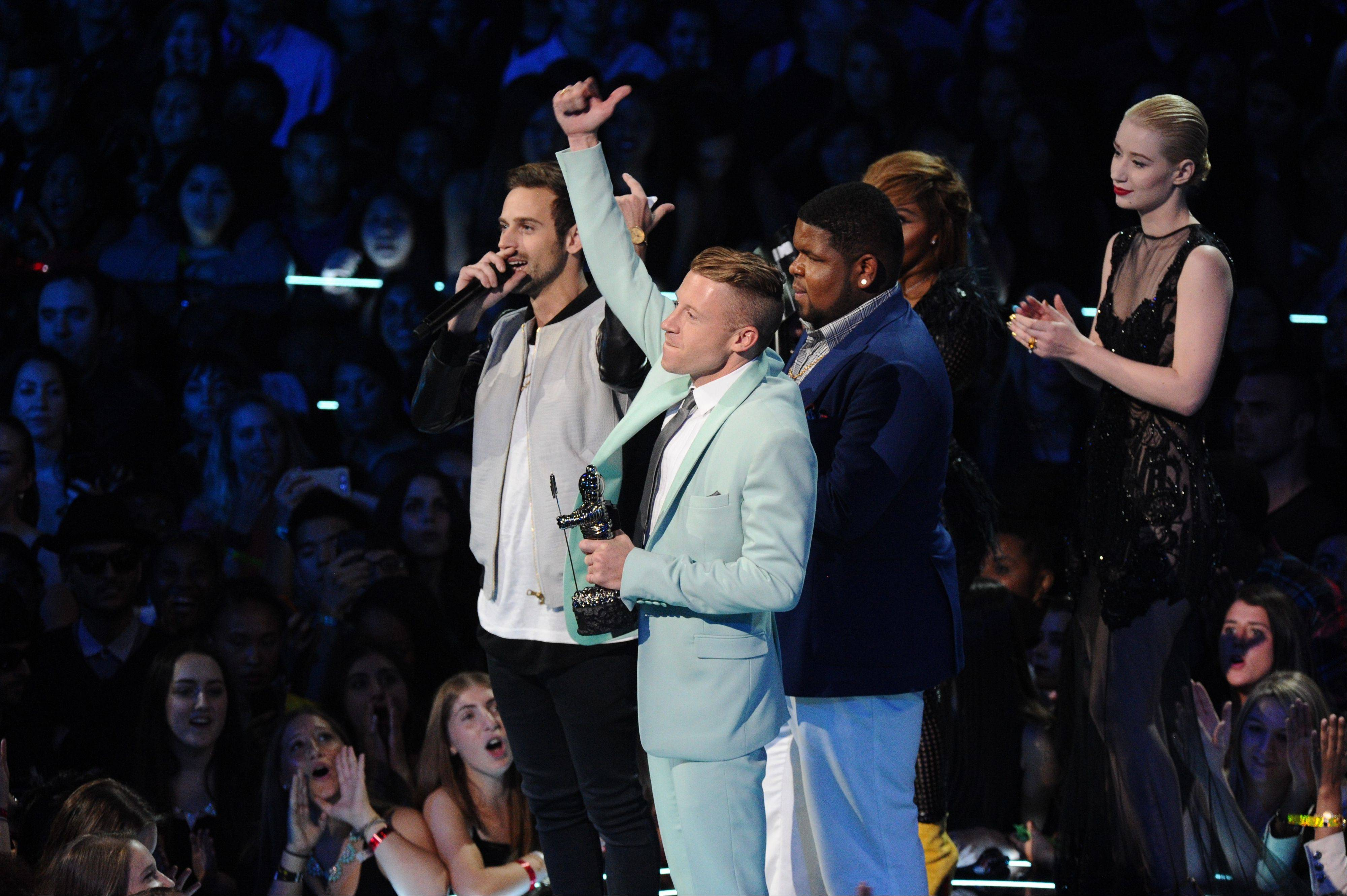 "Ryan Lewis, left, Macklemore, center, and Ray Dalton accept the award for best hip hop video for ""Can't Hold Us"" as presenters Iggy Azalea, right, and Lil' Kim look on, at the MTV Video Music Awards on Sunday, Aug. 25, 2013, at the Barclays Center in the Brooklyn borough of New York."