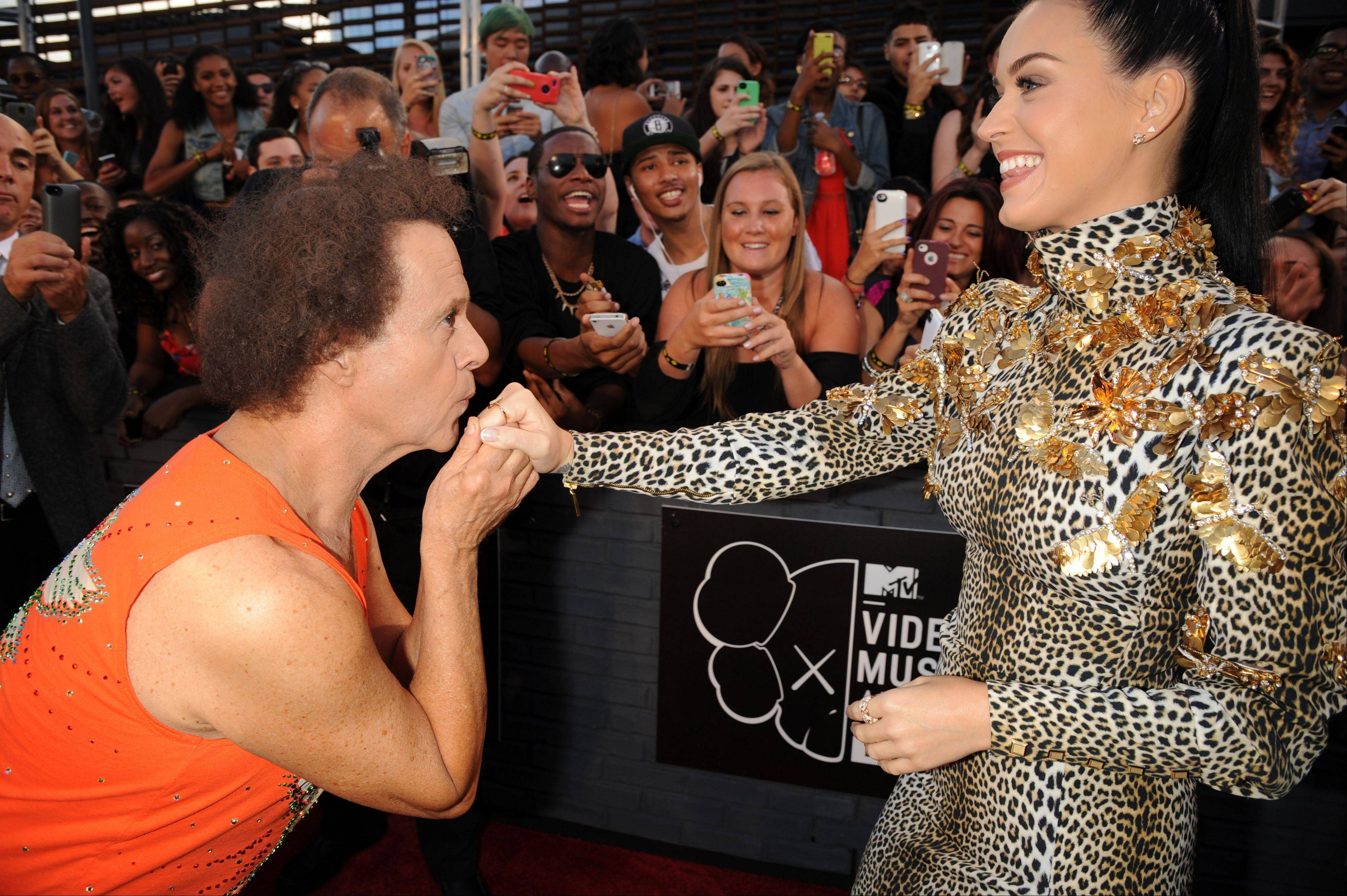 Fitness guru Richard Simmons, left, kisses the hand of singer Katy Perry at the MTV Video Music Awards on Sunday, Aug. 25, 2013, at the Barclays Center in the Brooklyn borough of New York.