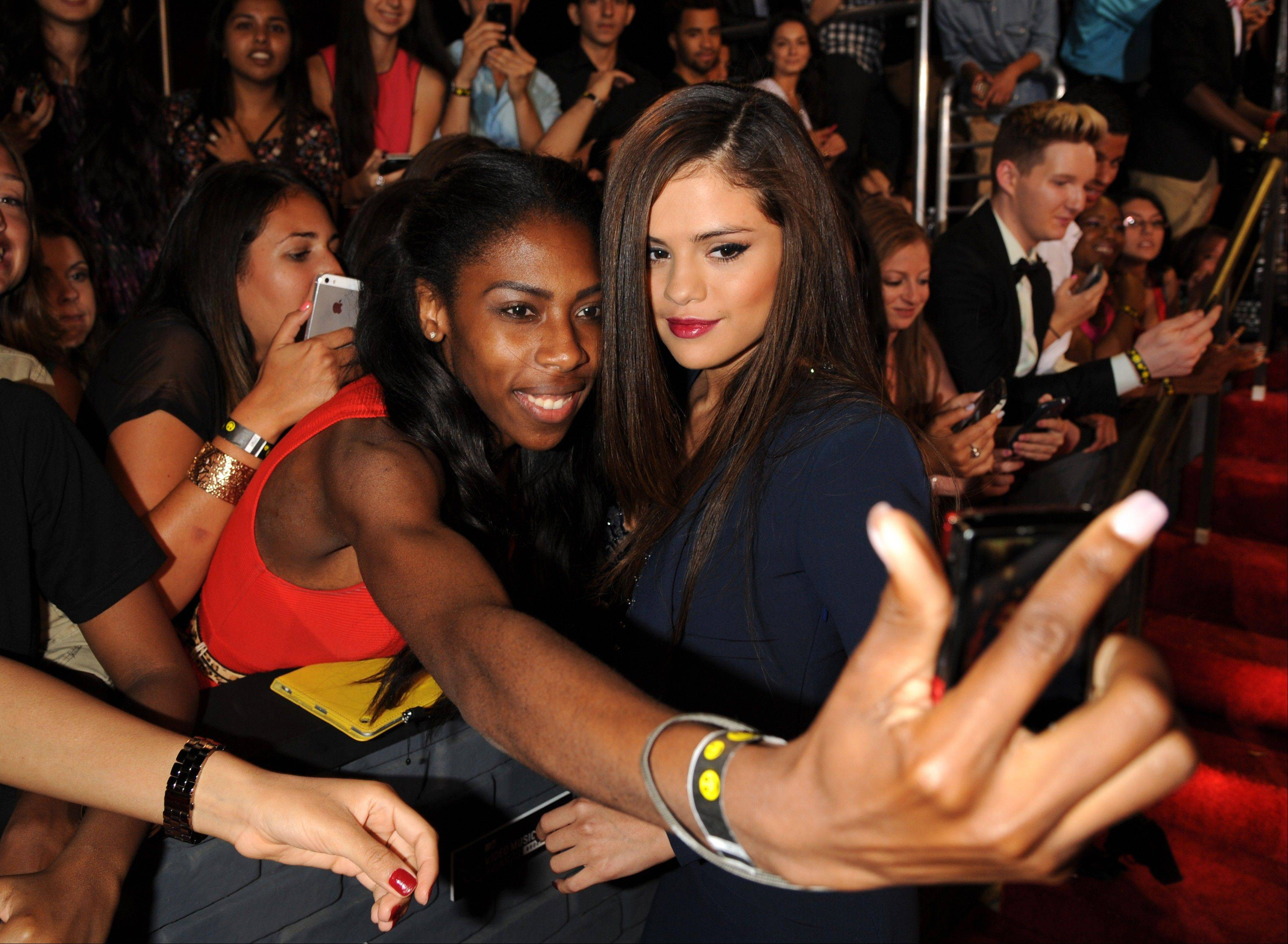 Selena Gomez poses with a fan at the MTV Video Music Awards on Sunday, Aug. 25, 2013, at the Barclays Center in the Brooklyn borough of New York