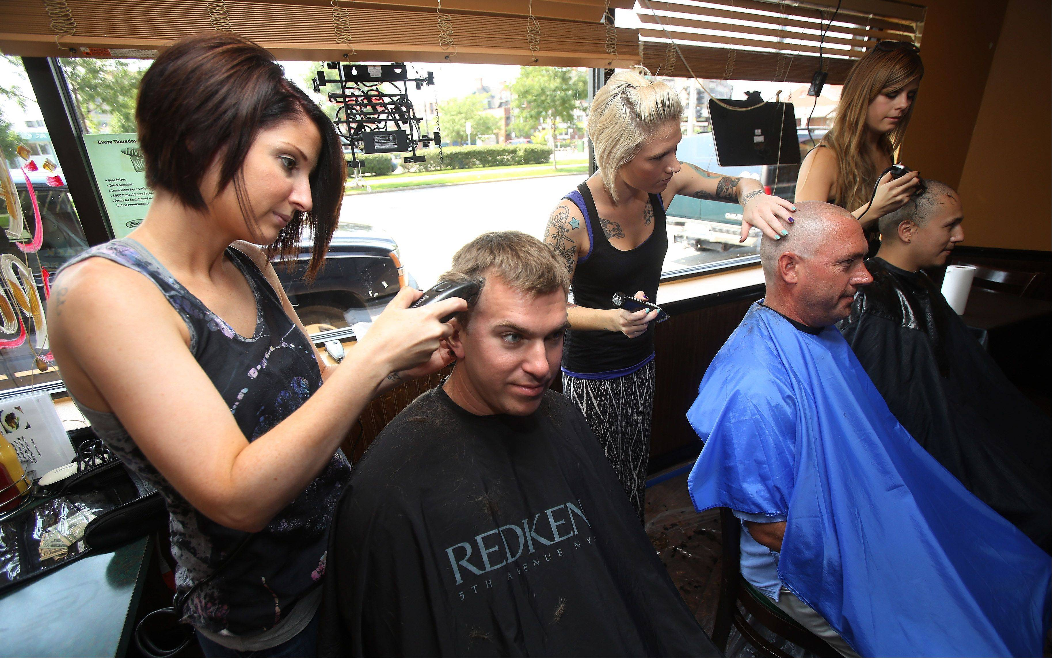 "Beautician Brittany Carroll, left, shaves the head of her husband, Buffalo Grove firefighter Jim, while other Buffalo Grove firefighters have their heads shaved during the Ryan ""McCancer"" Party Sunday at Eddie's in Arlington Heights. The charity fundraiser was in honor of 25-year-old Buffalo Grove firefighter Ryan McCarthy, of Rolling Meadows, who is battling lymphoma and benefitted the Leukemia & Lymphoma Society."