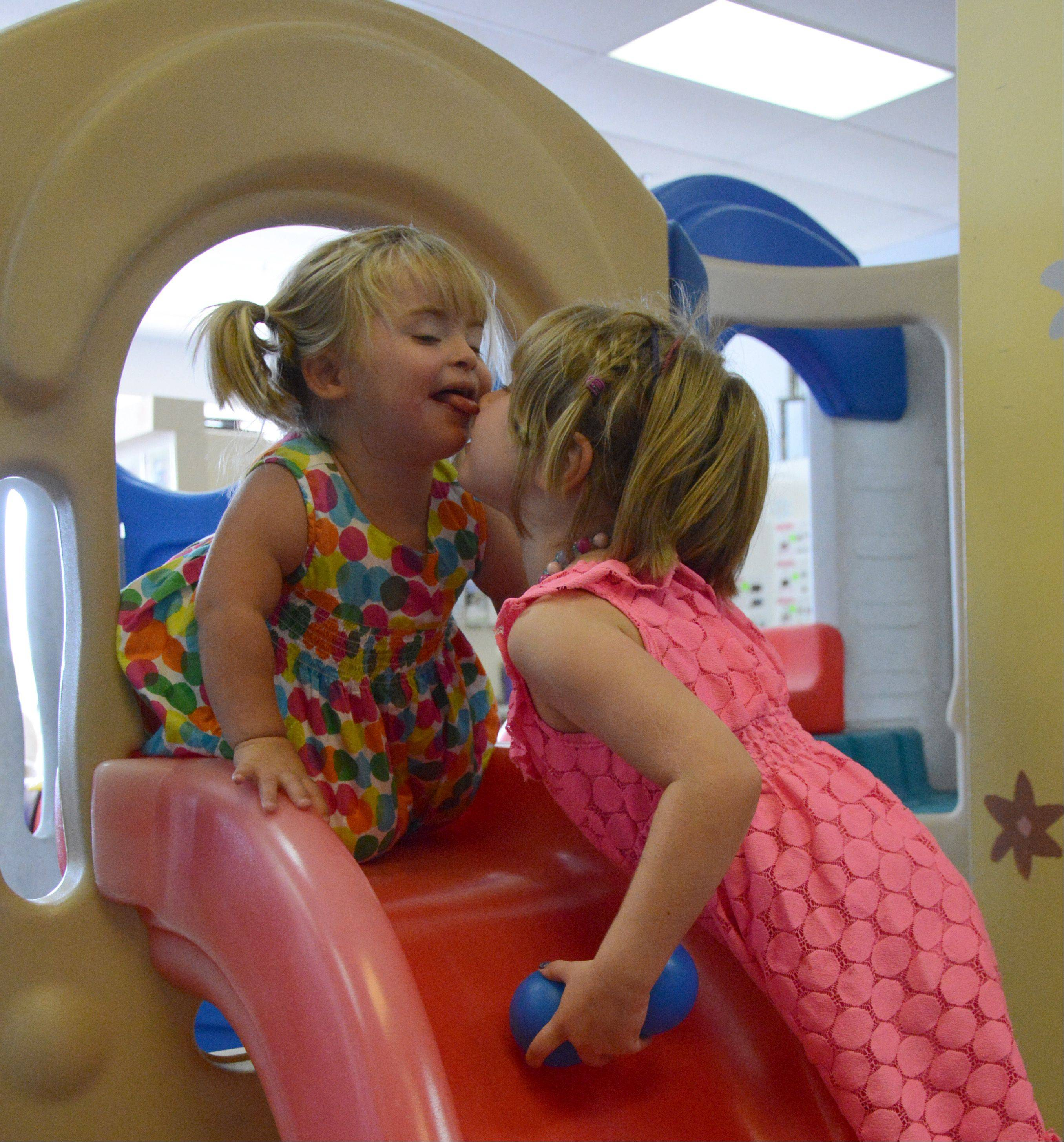 Rya Pospychala, 4, of New Hampshire, right, kisses sister Emani, 2, at GiGi's Playhouse in Hoffman Estates. GiGi's playhouse is in the process of building a new facility several miles from the current facility.