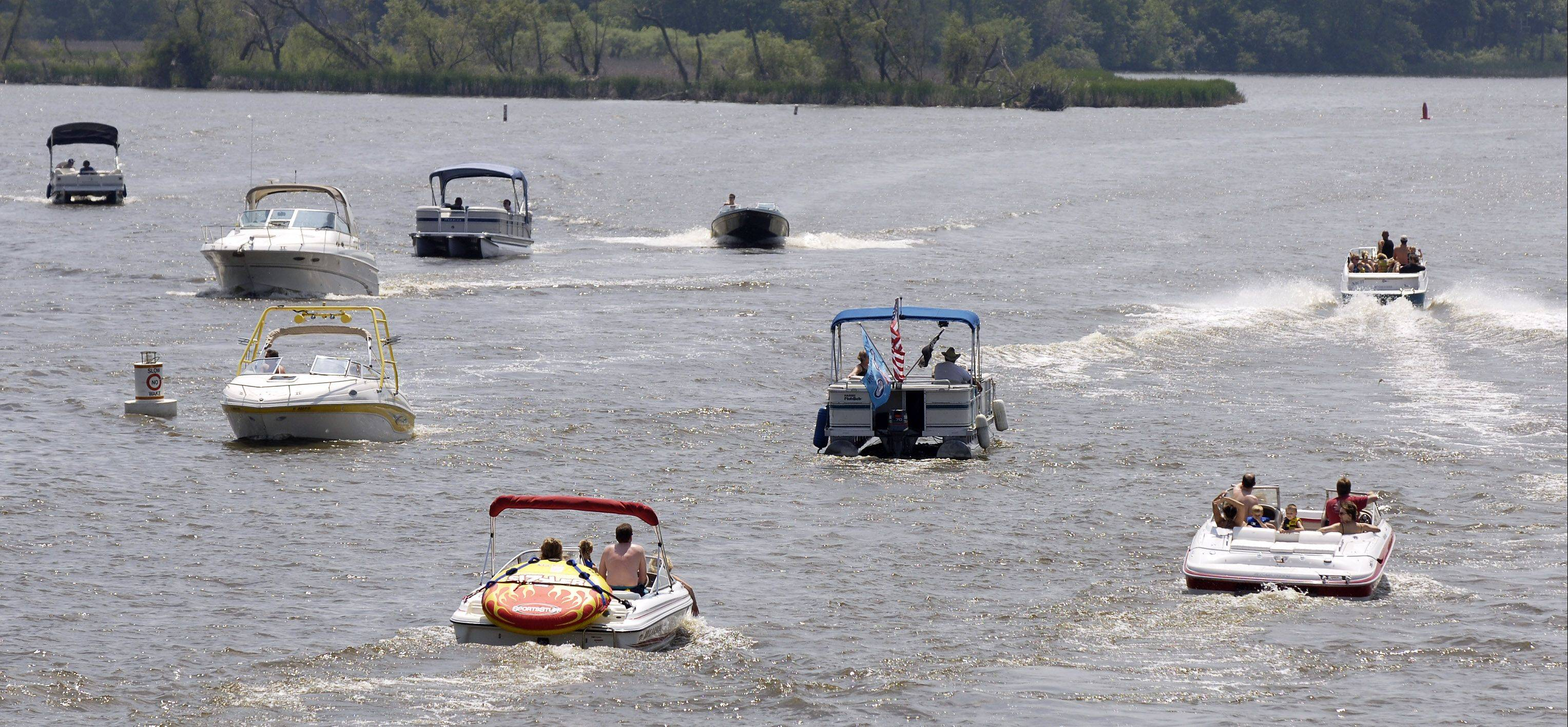 Boats travel under the Grass Lake Road bridge on the Chain O' Lakes. The family of Tony Borcia who was killed on the Chain O' Lakes are lobbying for new stricter boating laws including the suspension of a driver's license when a boater is found to be over the legal threshold for intoxication and also requiring the operators of a watercraft towing a person behind a boat to display an orange flag to alert others.