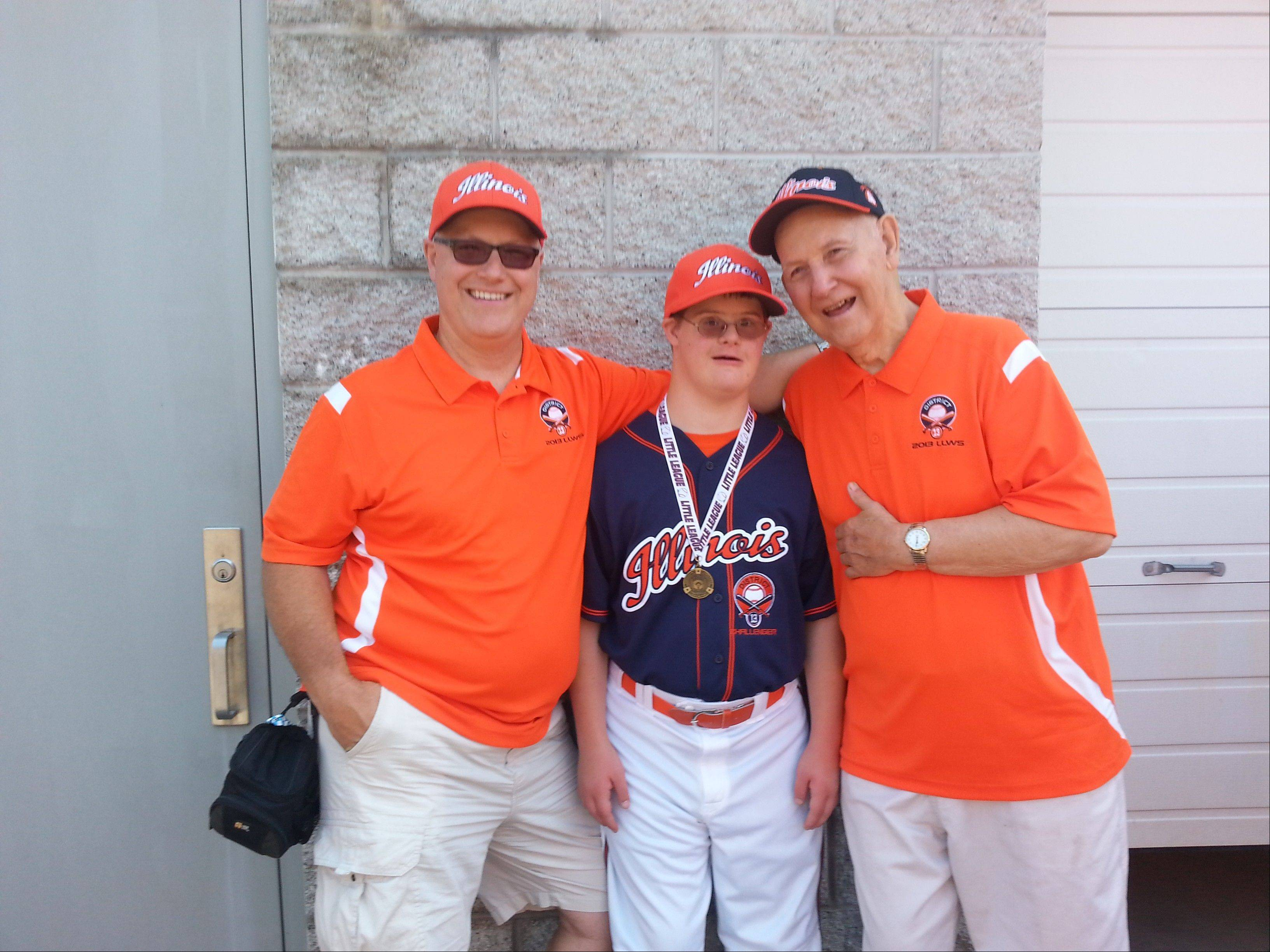 Sharing a moment that was three generations and 41 years in the making, former Little League Baseball World Series player Peter Vargulich, left, of St. Charles, and his father and former coach Tom Vargulich, right, cheer on Tommy Vargulich, 16. Tommy became the third generation to play on that famous field with his participation Saturday in an exhibition game featuring young people with disabilities.