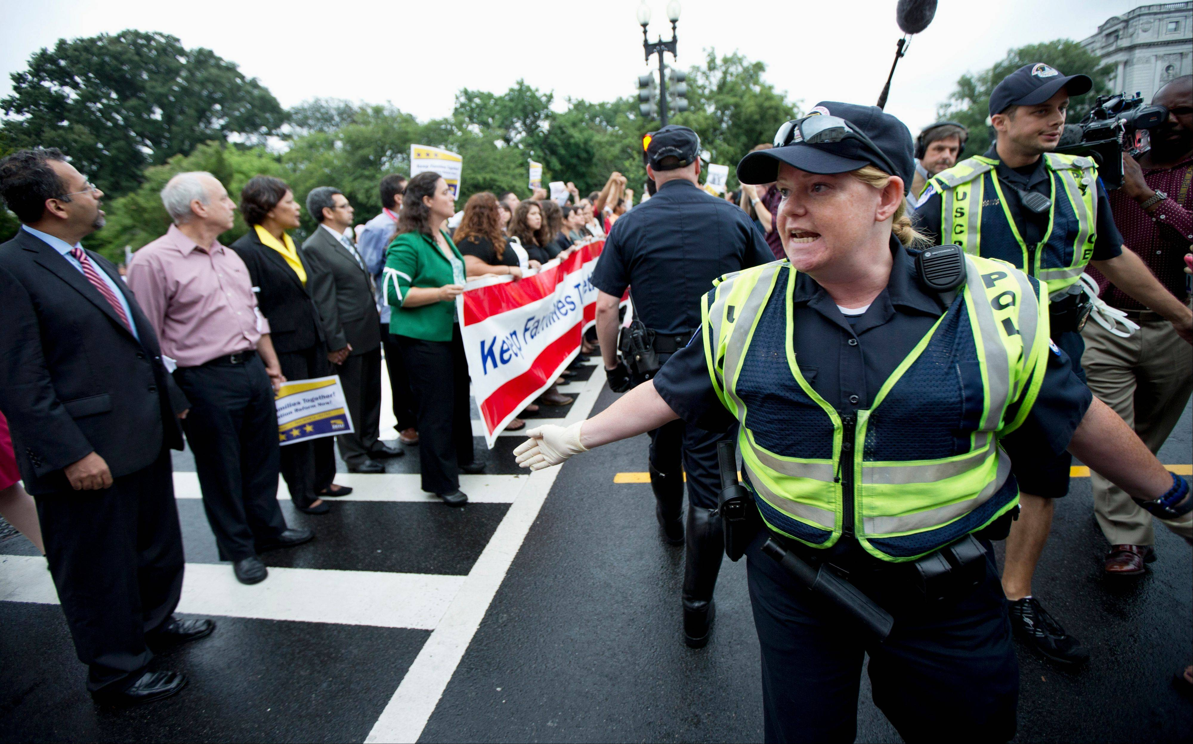 Capitol Hill Police officers try to clear a street that was blocked by immigration reform supporters during a rally protesting immigration policies and the House GOP's inability to pass a bill that contains a pathway to citizenship.