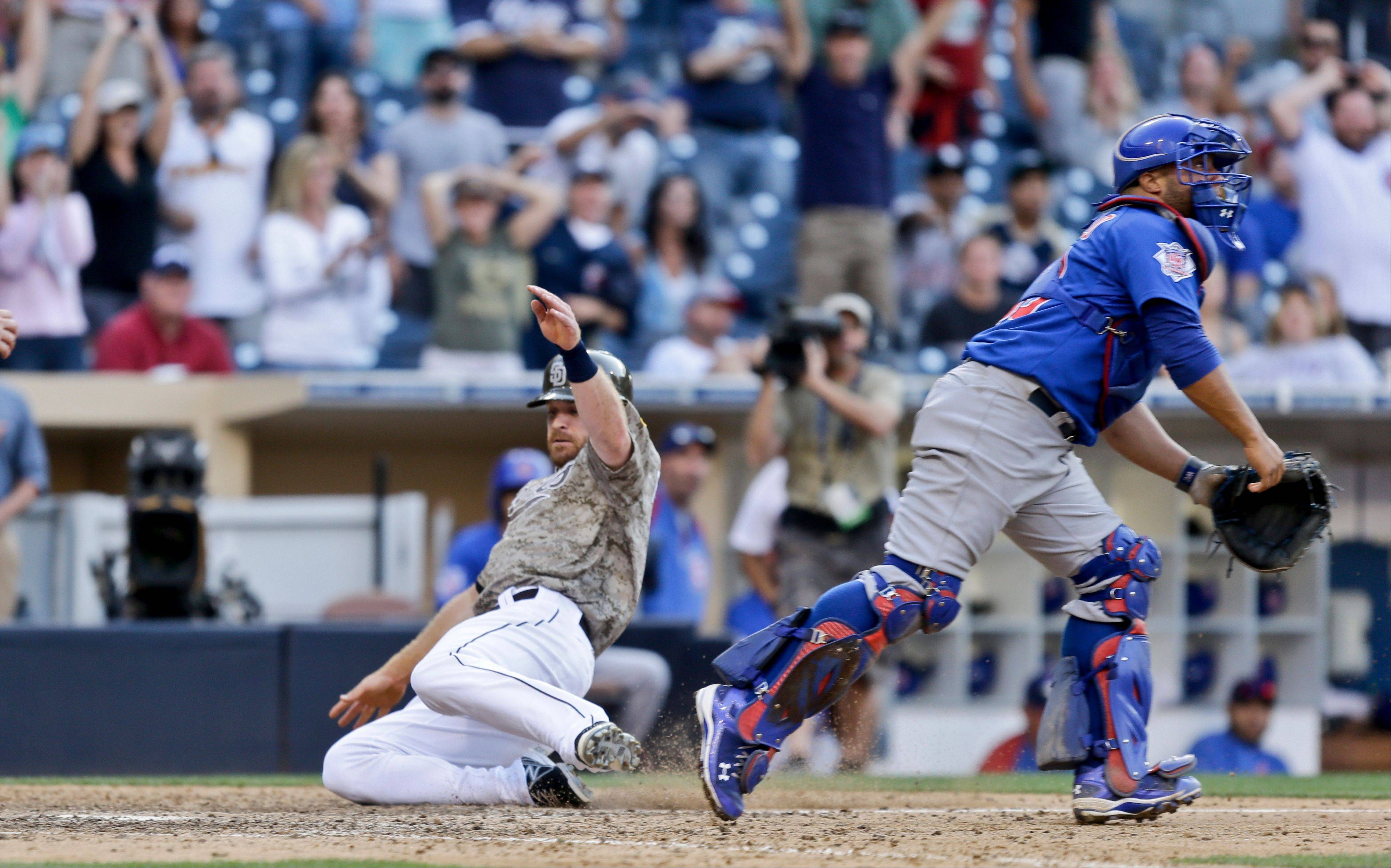 San Diego Padres' Logan Forsythe slides in safely with the game winning run as Chicago Cubs catcher Welington Castillo chases the late throw in the fifteenth inning of a baseball game won 3-2 by the Padres Sunday, Aug. 25, 2013, in San Diego.