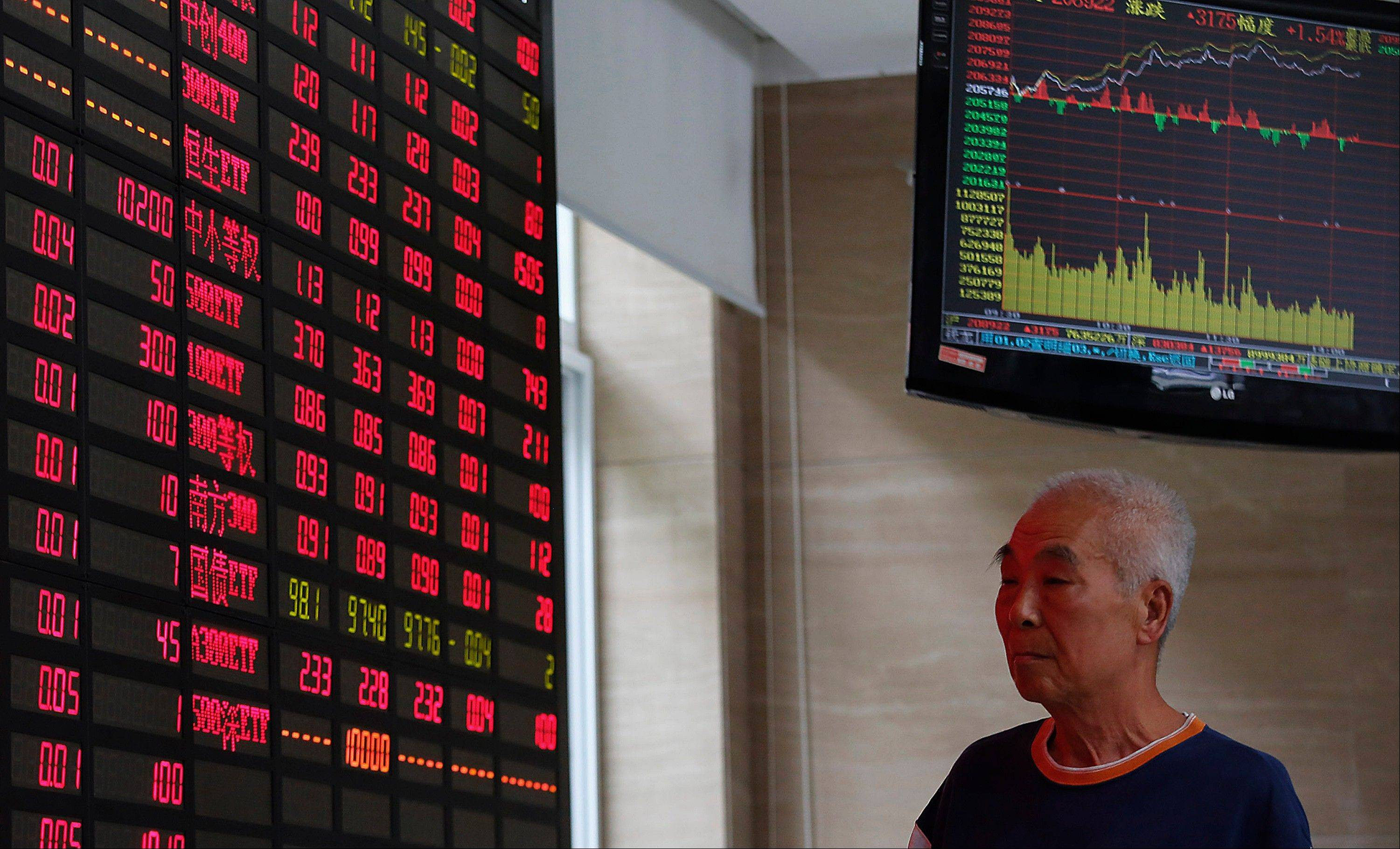 An investor looks at a stock prices monitor at a private securities company Monday in Shanghai, China. Asian stock markets mostly rose Monday after expectations for an imminent phasing out of the Federal Reserve�s monetary stimulus program began to fade.