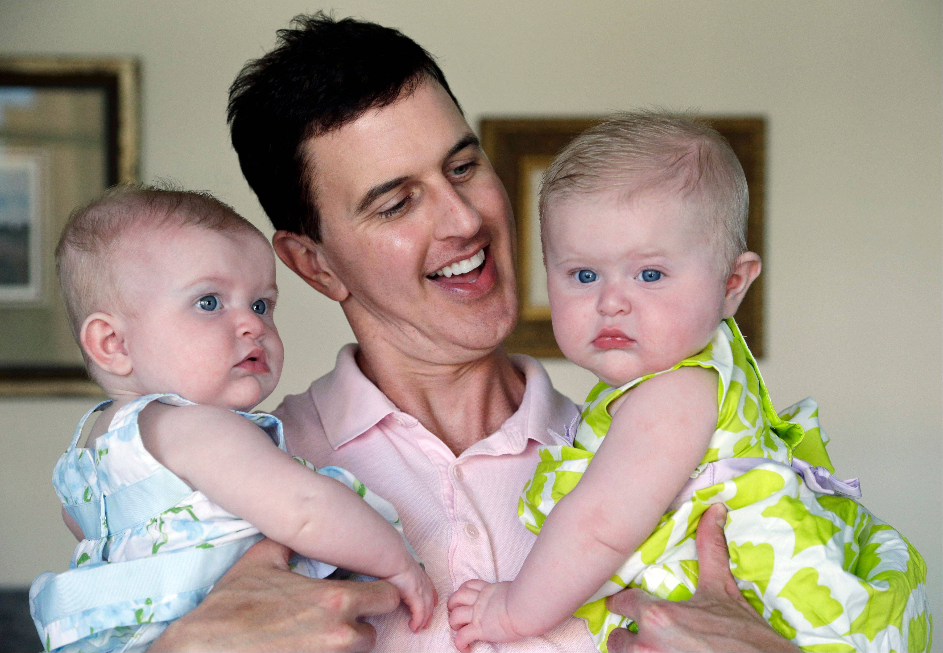 Trey Powell holds his 6-month-old daughters Kylan, left, and Ashton in their home in Seattle.