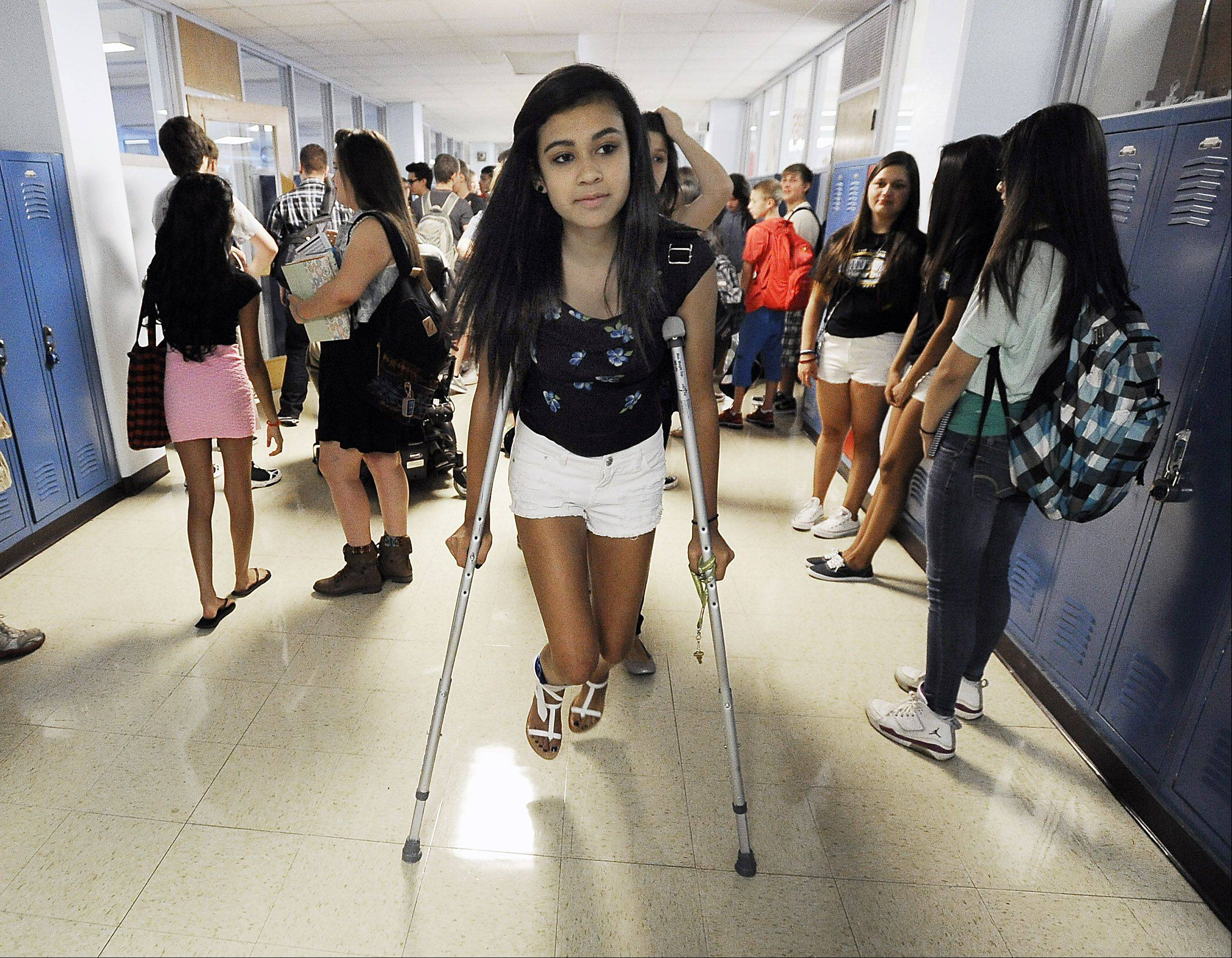 Freshman Aisis Julian, 14, has a tough start to her first day back to school at Maine West High School, maneuvering through a hallway full of classmates after having injured her ankle in volleyball tryouts.