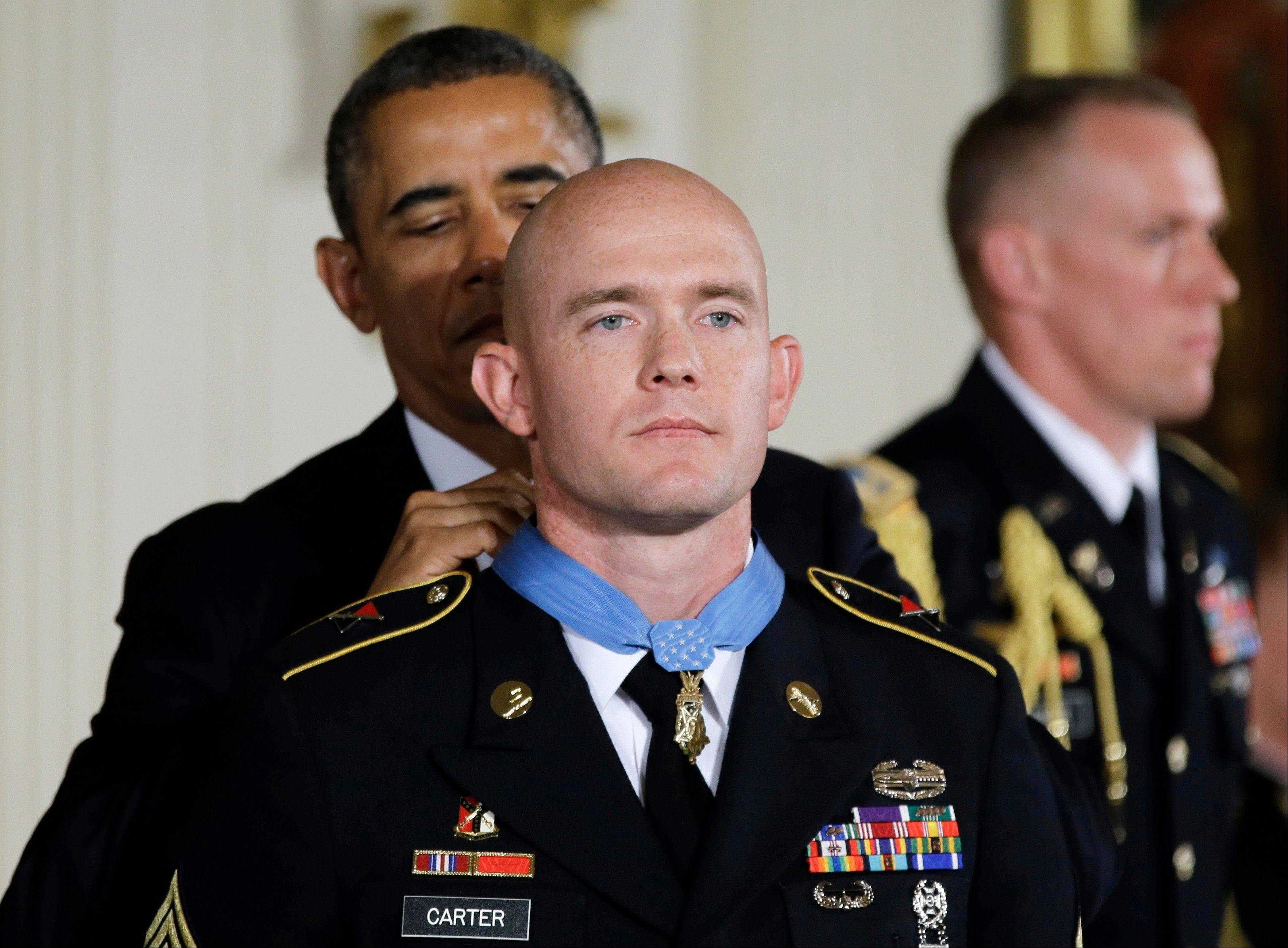 President Barack Obama awards U.S. Army Staff Sgt. Ty M. Carter the Medal of Honor for conspicuous gallantry Monday, during a ceremony in the East Room of the White House in Washington.