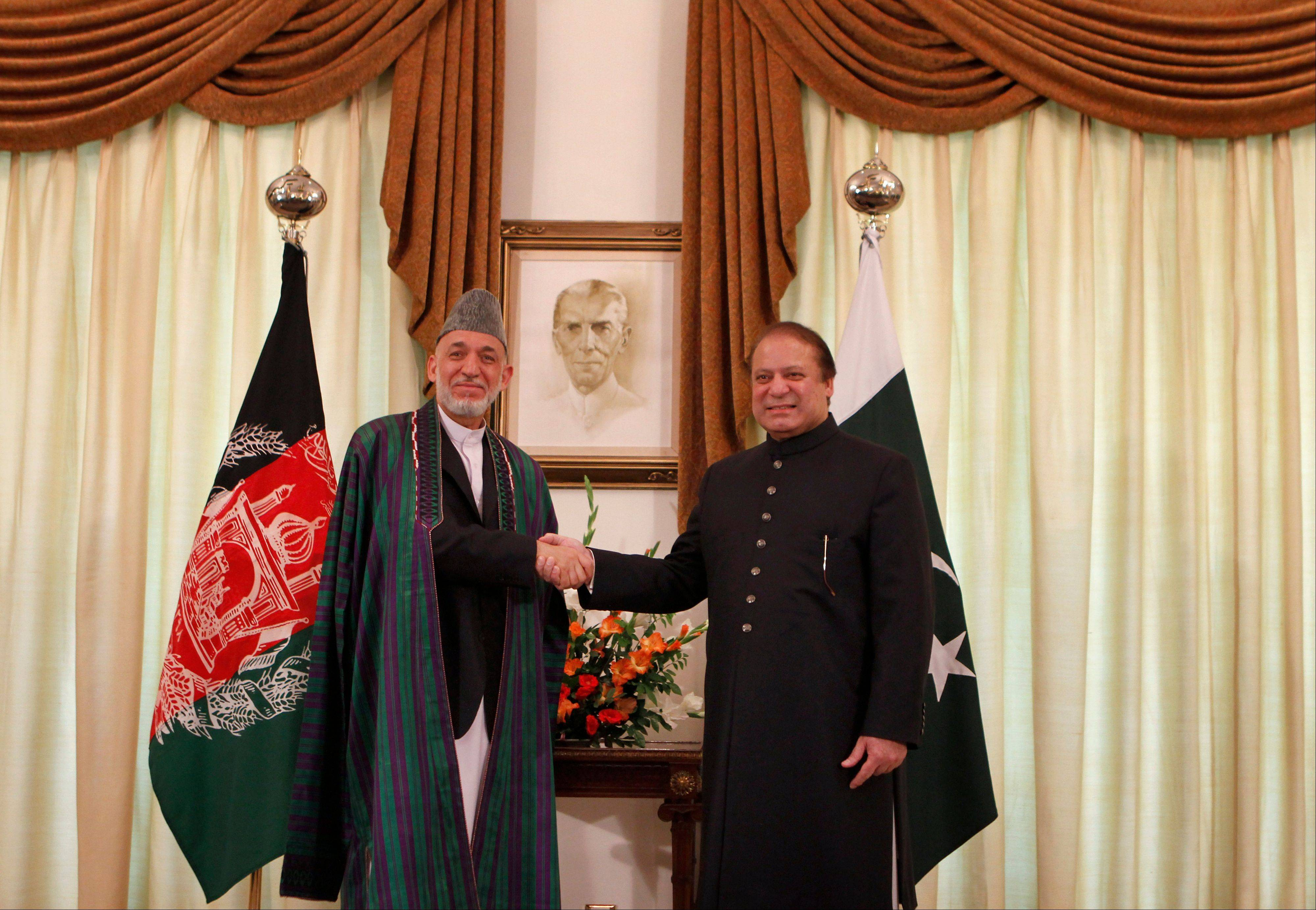 Afghan President Hamid Karzai, left, shakes hand with Pakistani Prime Minister Nawaz Sharif prior to their meeting in Islamabad, Pakistan, Monday. Afghanistan�s president urged neighboring Pakistan to facilitate peace talks with the Taliban during a visit to Islamabad on Monday, but expectations were low in both countries that much progress would be made in jump-starting negotiations.