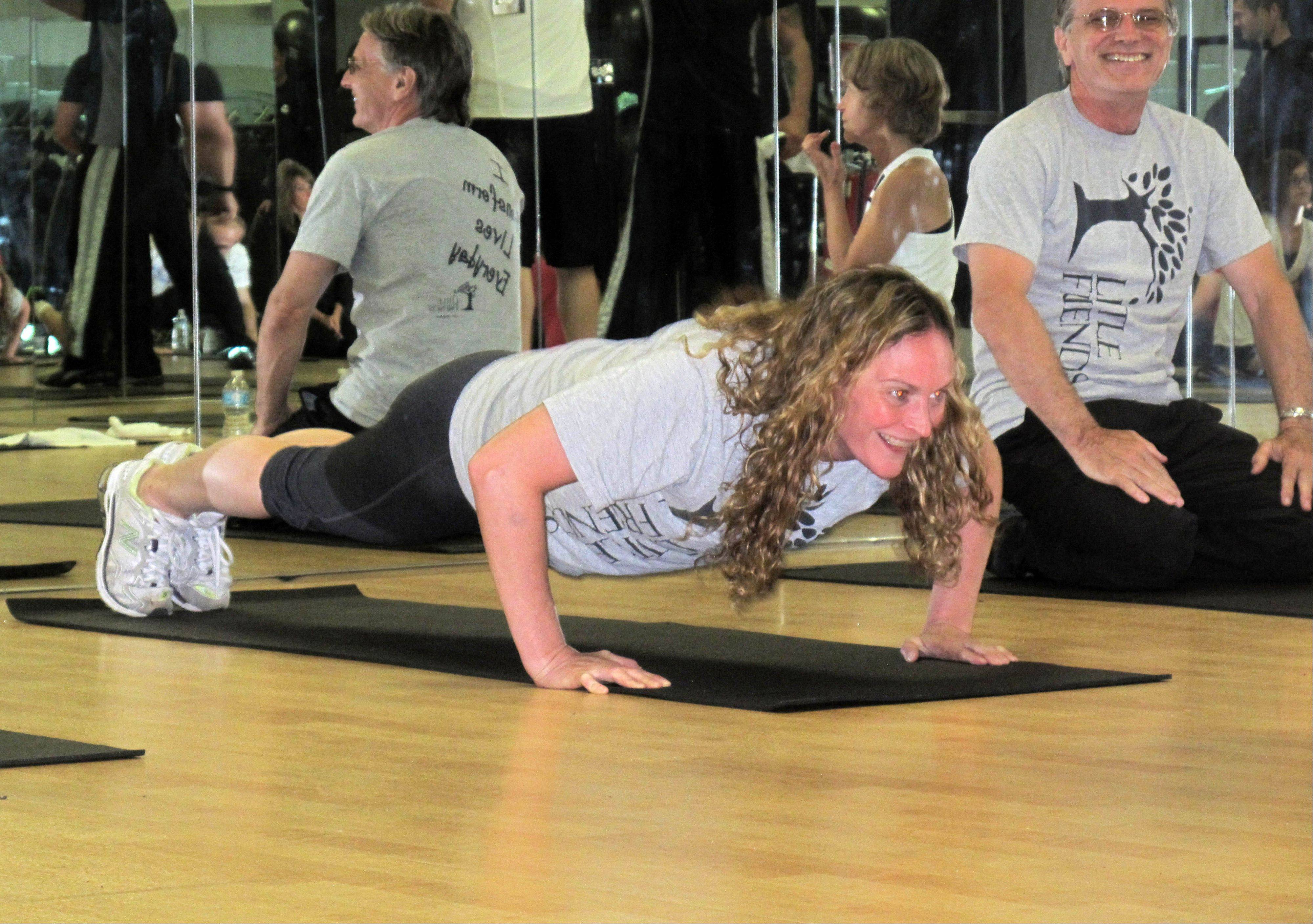 Kari Krzemkowski, director of finance for Little Friends in Naperville, does her first round of 10 push-ups during the Big Push-ups for Little Friends fundraiser hosted by Midwest Fit Club. The event challenged teams of people to take turns doing push-ups for an hour and the gym donated 5 cents for every push-up completed in 24 hours.