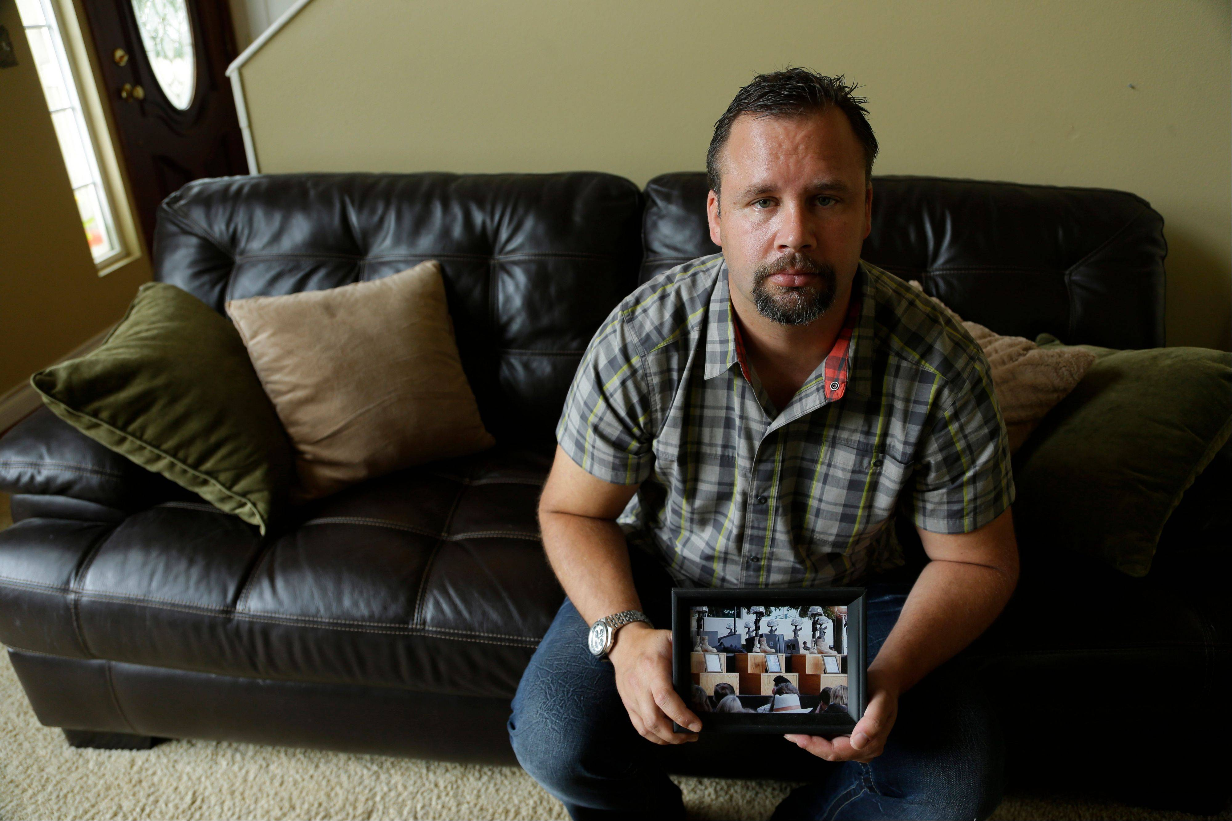 Retired U.S. Army Staff Sgt. Shawn Manning holds a photograph from the memorial for victims of the 2009 mass shooting at Fort Hood, Texas, at his home in Lacey, Wash. Manning still carries two bullets in his body from the shooting that killed 13 and wounded over 30.