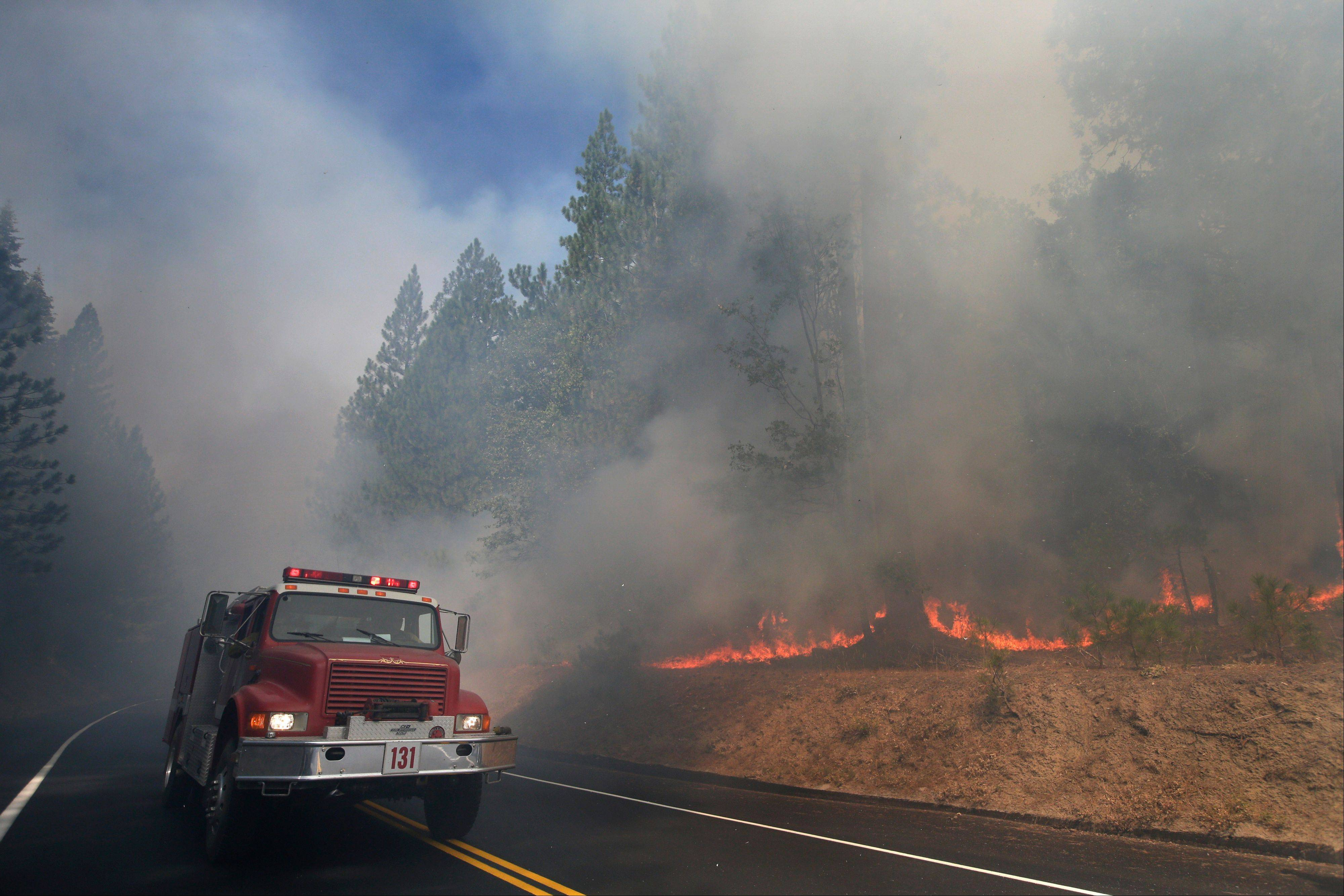 A fire truck drives past burning trees as firefighters continue to battle the Rim Fire near Yosemite National Park, Calif., Monday. Crews working to contain one of California�s largest-ever wildfires gained some ground against the flames threatening San Francisco�s water supply, several towns near Yosemite National Park and historic giant sequoias.