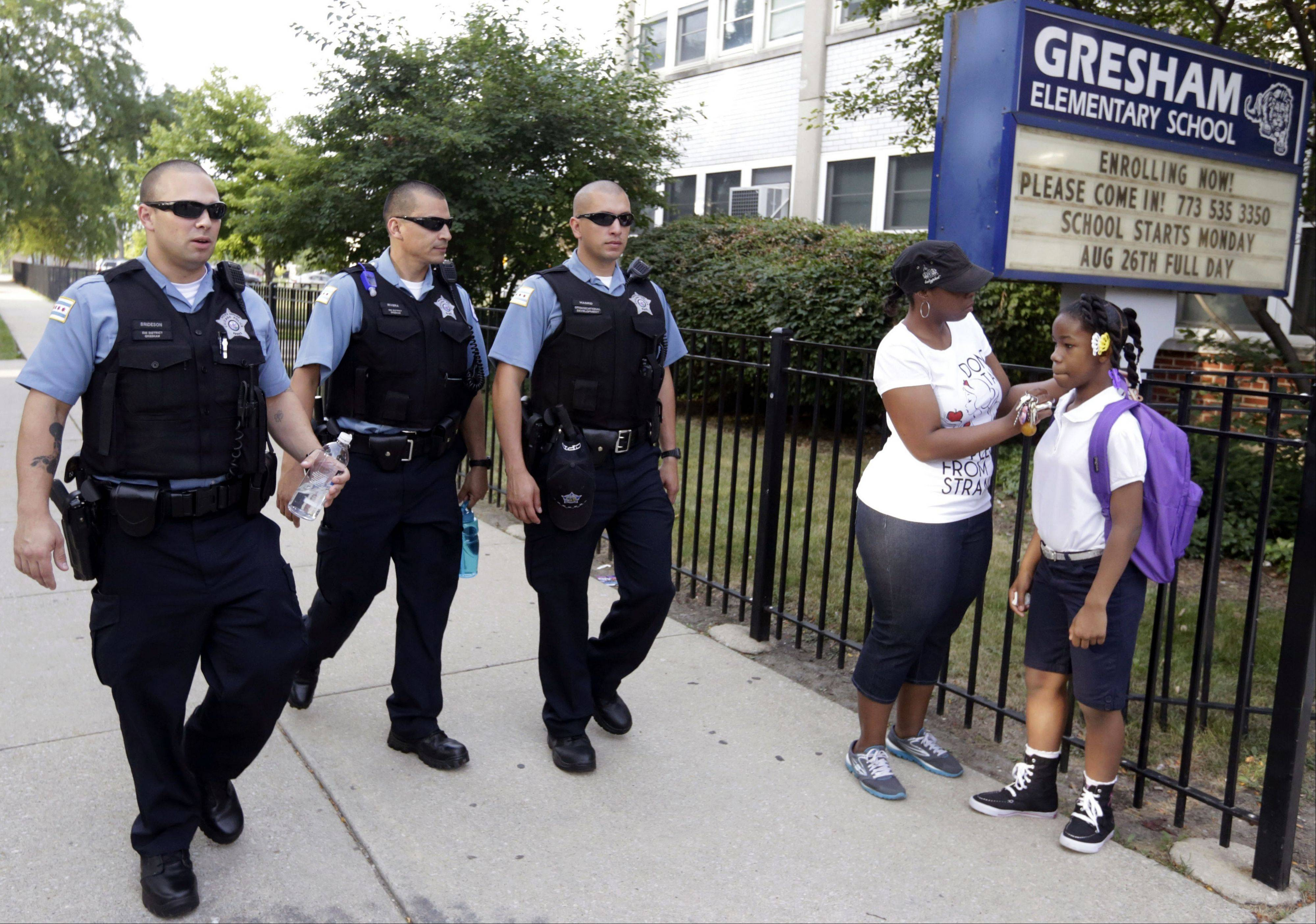 Chicago police patrol the neighborhood as Crystal Stoval delivers her niece Kayla Porter from their South Side home to Gresham Elementary School on the first day of classes Monday.