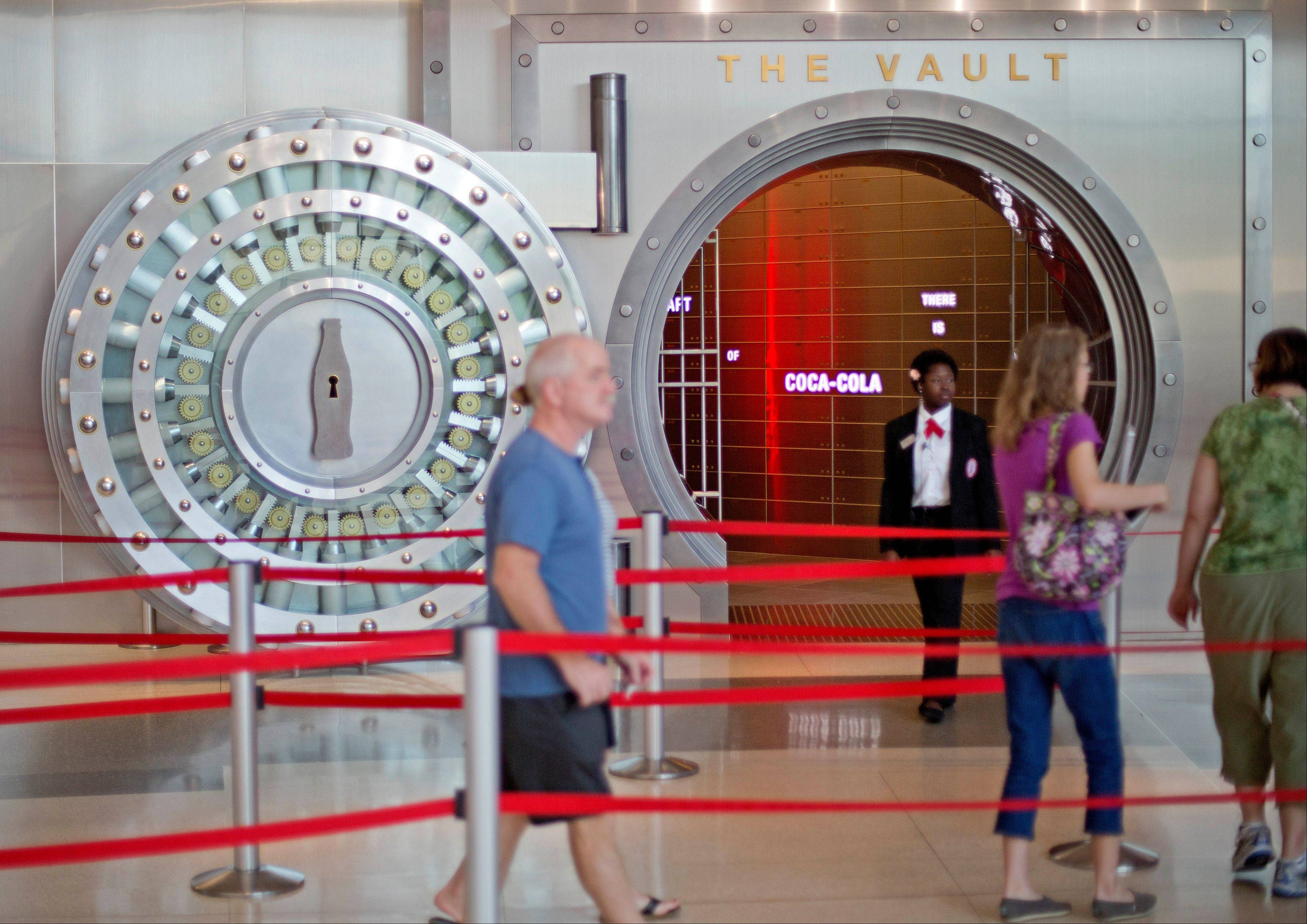 "A tour group enters the vault exhibit containing the ""secret recipe"" for Coca-Cola at the World of Coca-Cola museum in Atlanta. The 127-year-old recipe for Coke sits inside an imposing steel vault bathed in red security lights, while security cameras monitor the area to make sure the fizzy formula stays secret."
