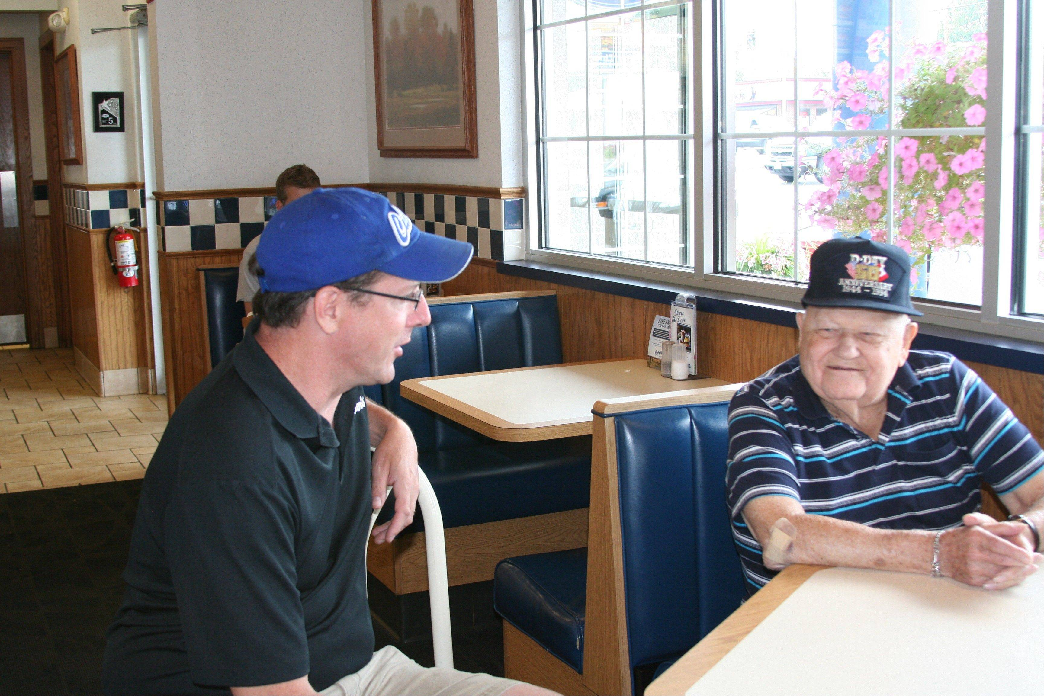 COURTESY OF CULVER'S Culver's General Manager Jesse Jarrett in Zion talks with longtime customer George Houchin of Waukegan.