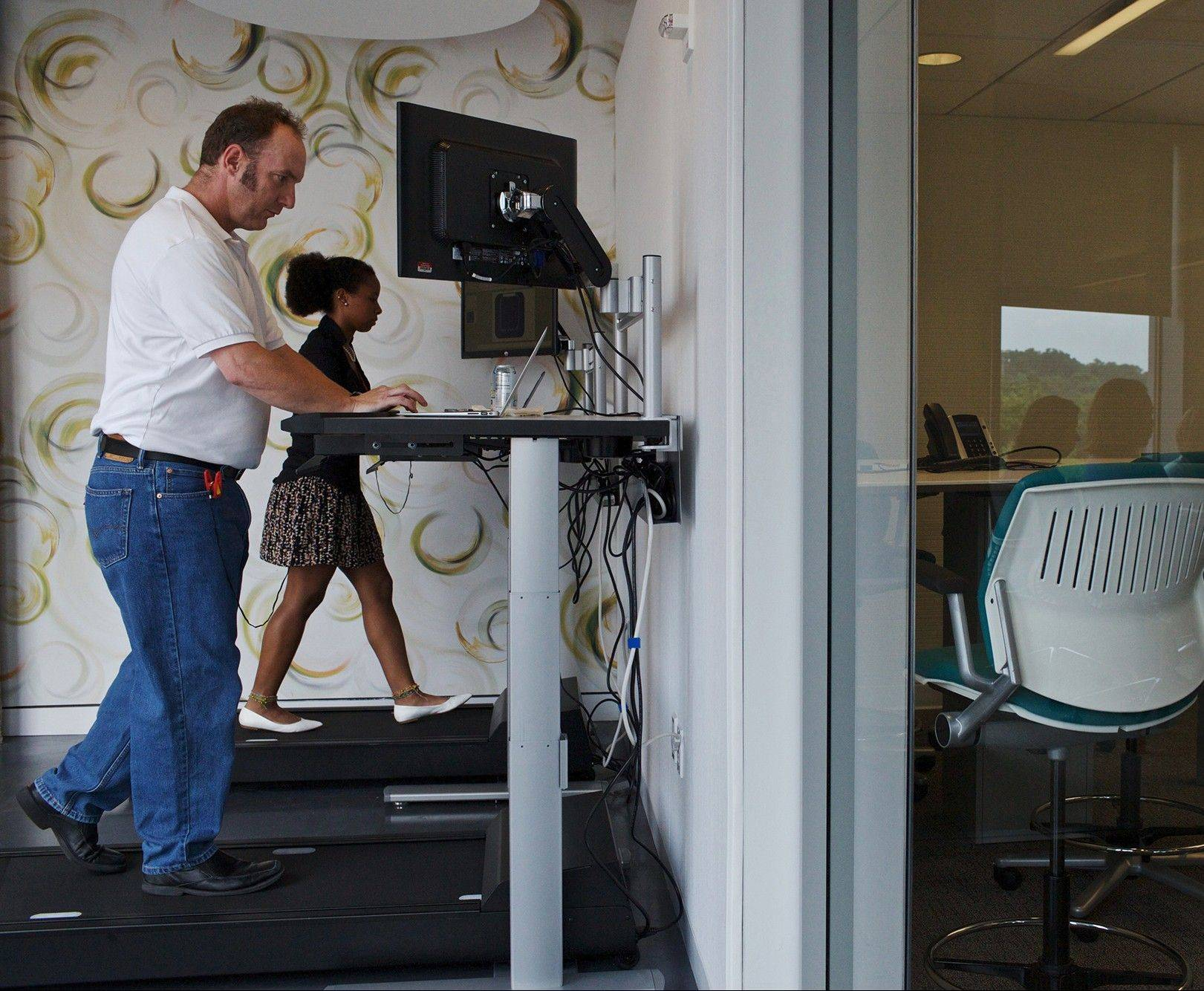 Michelle Schneider and Dave Dunn use treadmill desks at Evolent, a health care startup in Arlington, Va. Researchers are trying to determine whether the equipment allows people to burn off glucose that accumulates in the bloodstream.