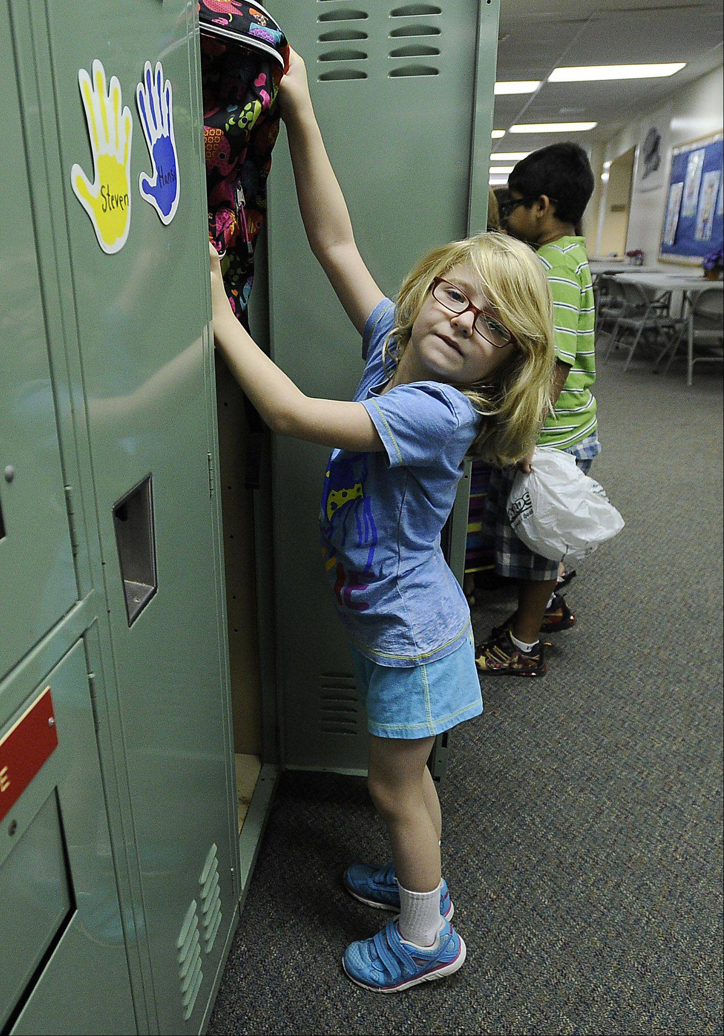 Abby Riskus, 7, has difficulty reaching the top shelf of her locker to store school supplies on the first day of school Monday at Frank C. Whiteley Elementary School in Hoffman Estates.