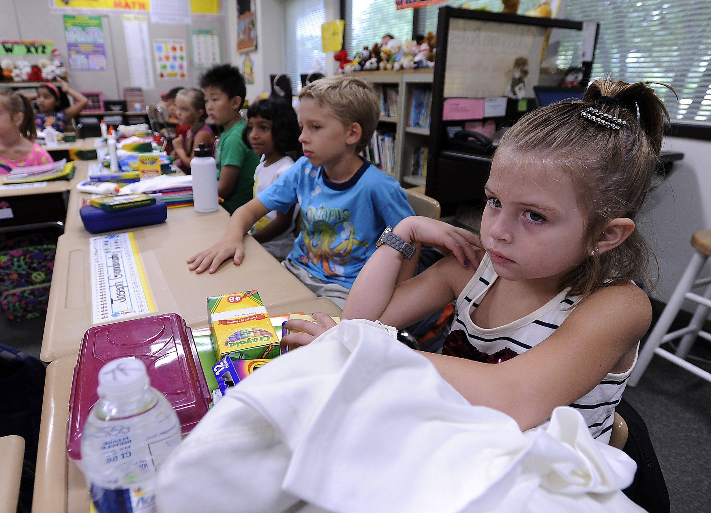 Tessa Ruttenberg, 7, sits in her second-grade class with all her school supplies on the first day of school Monday at Frank C. Whiteley Elementary School in Hoffman Estates.